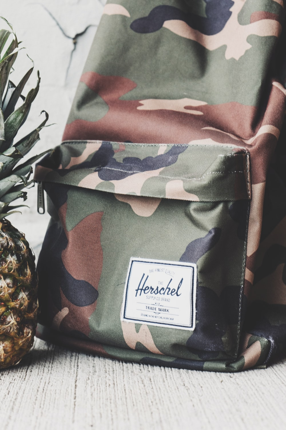 Cropped shot of a camo backpack and part of a pineapple.