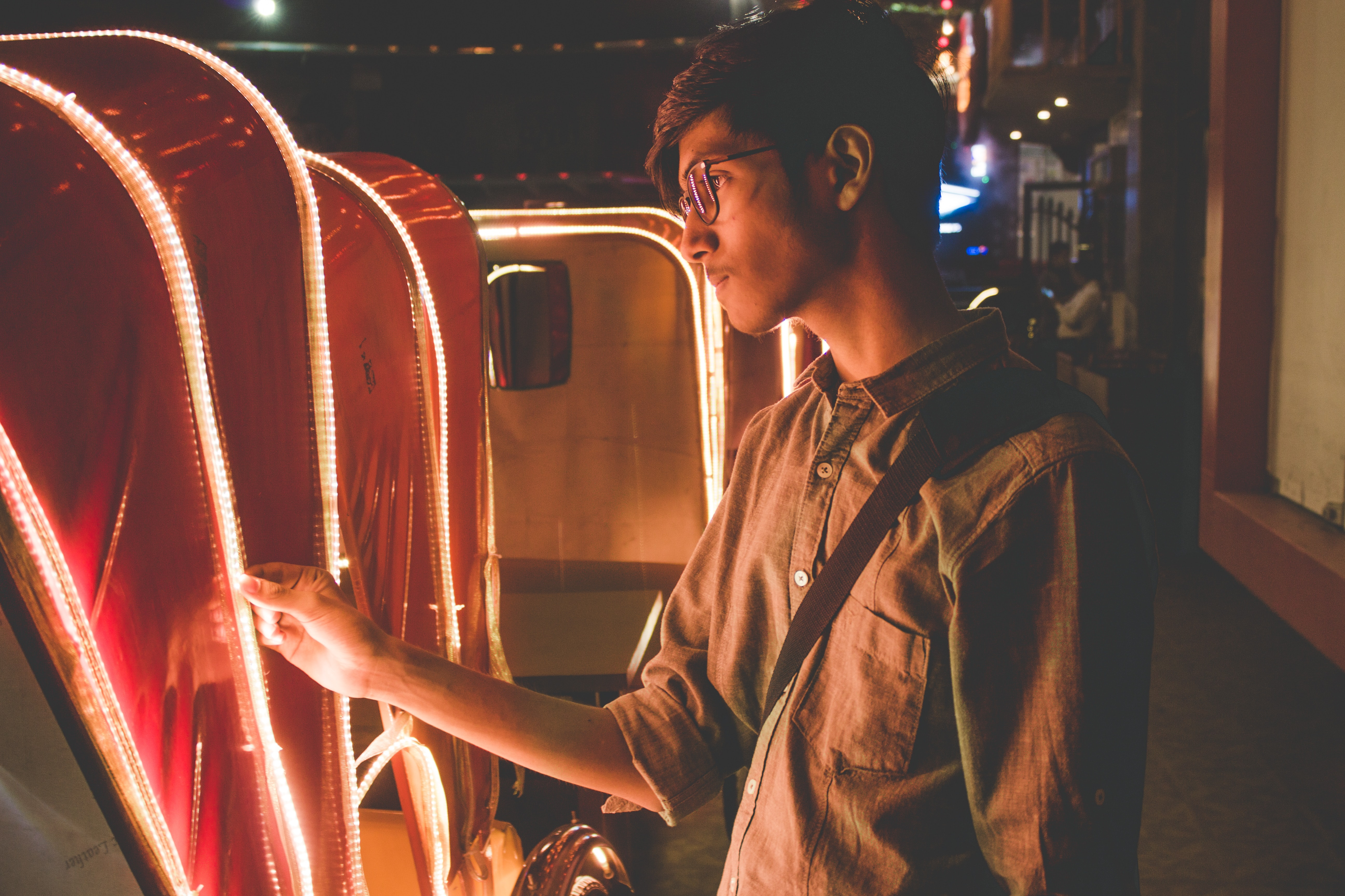 Young hipster man looks at the lights lining a carriage on a dark city street