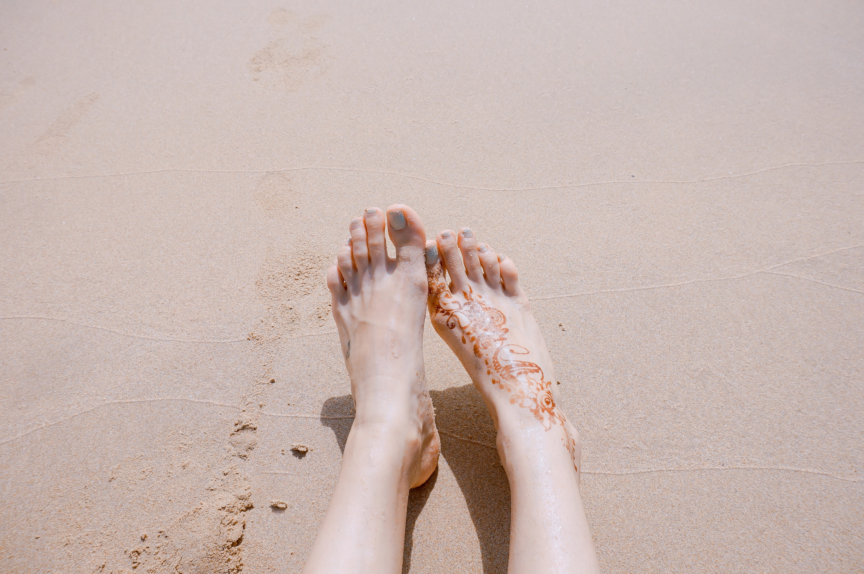 selective focus photography of feet with tattoo on sea sand