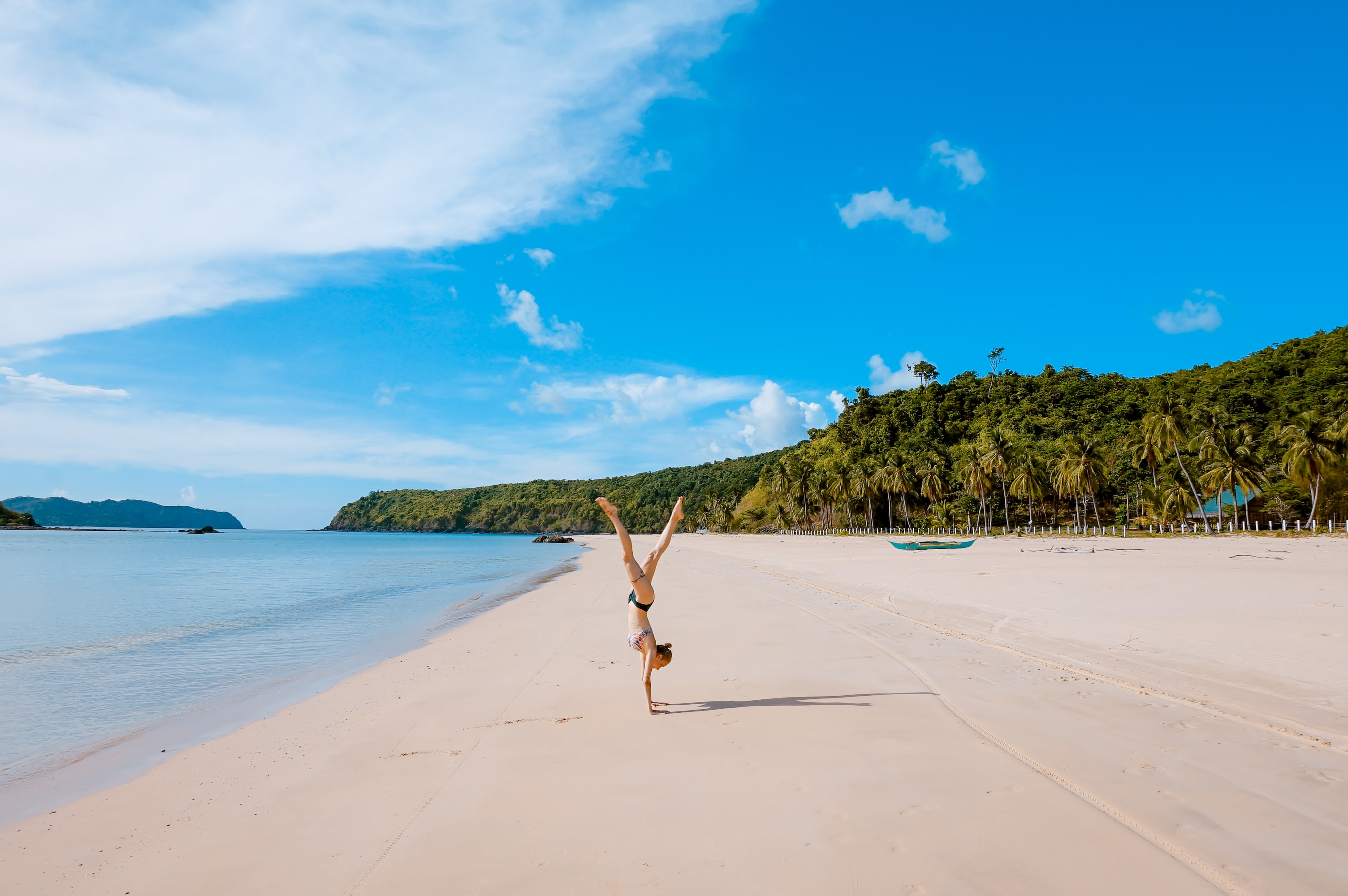 A woman doing a handstand on a sunny day on the beach in Palawan
