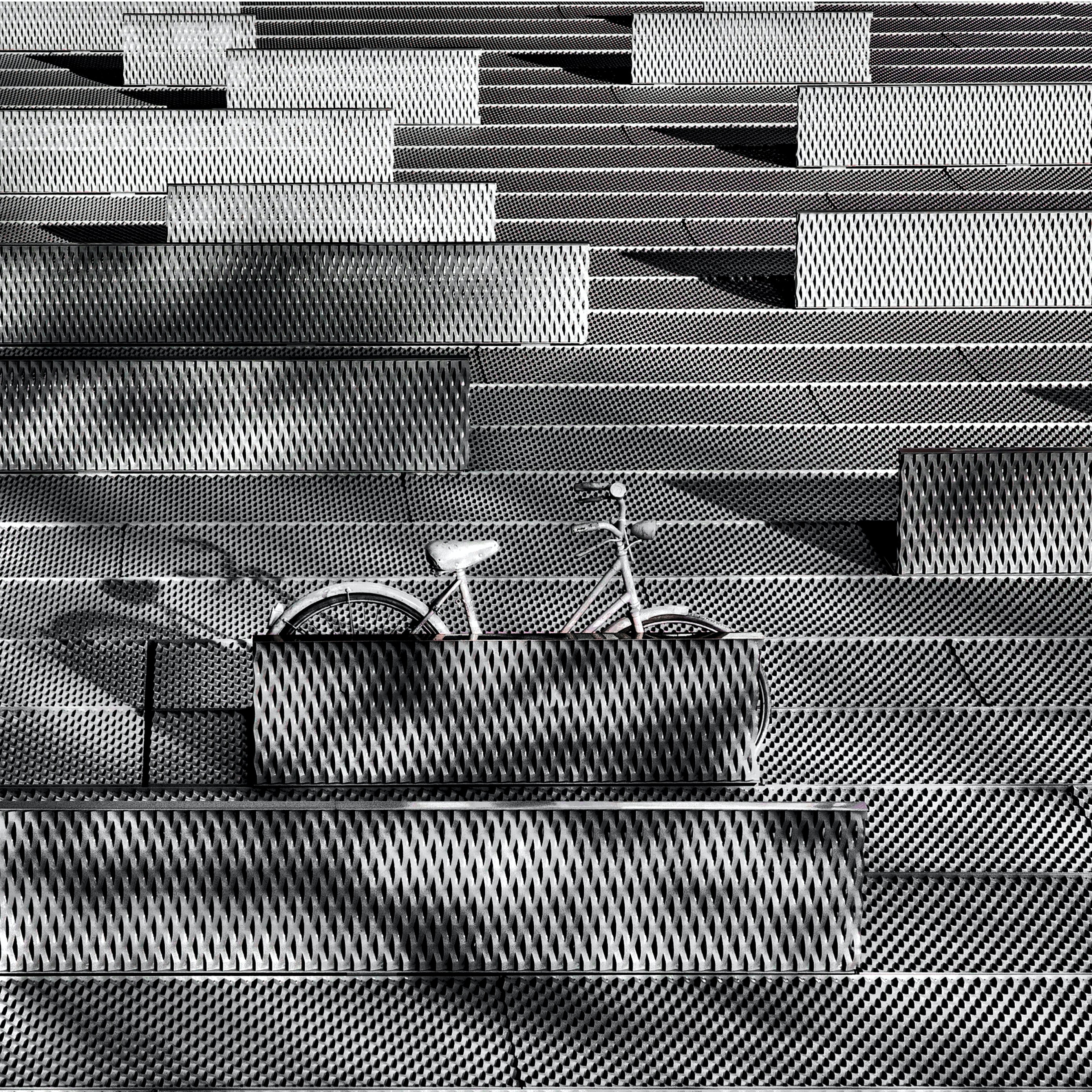 A gray bicycle parked on a gray latticework surface