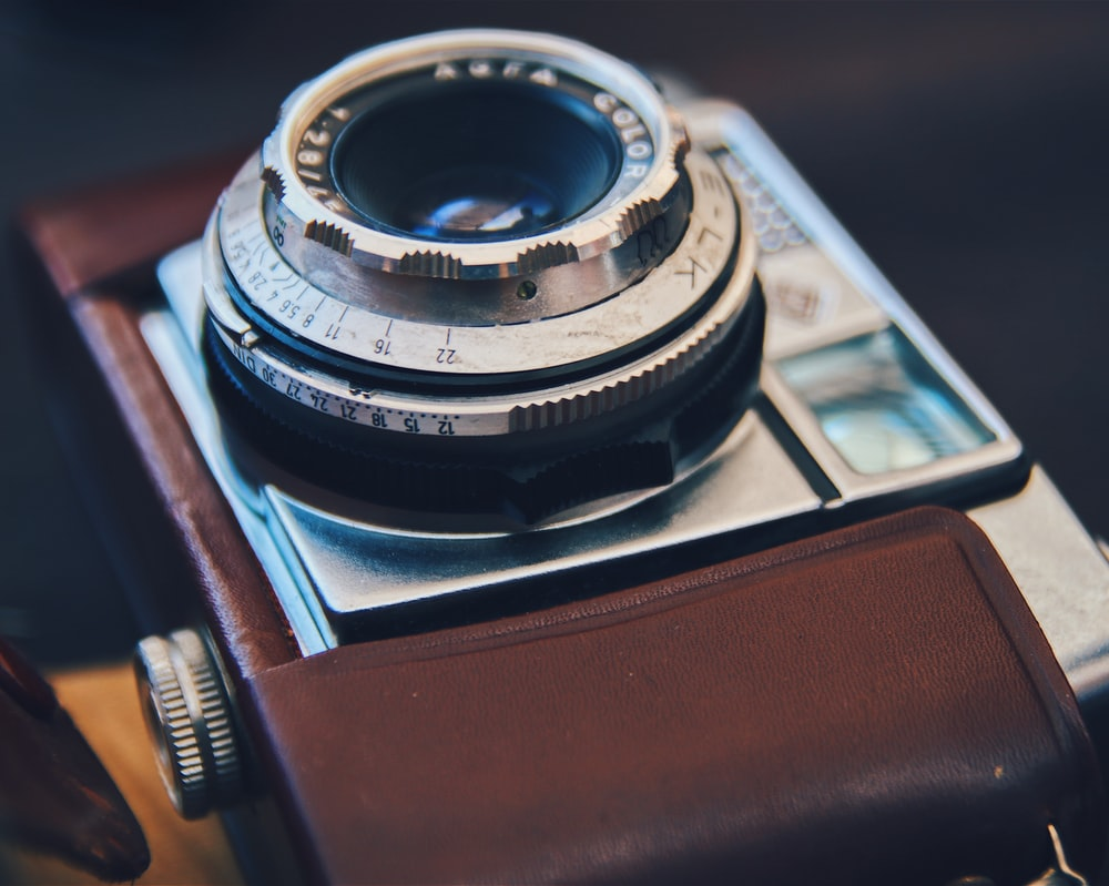 silver DSLR camera with brown leather case