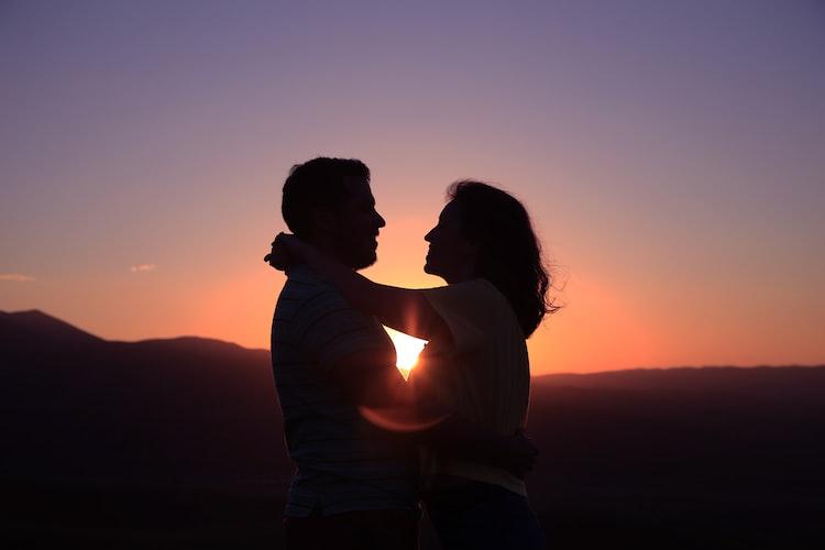 casal abraçado ao pôr do sol
