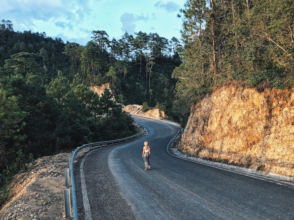 woman walking on gray asphalt road in between trees and rock formations