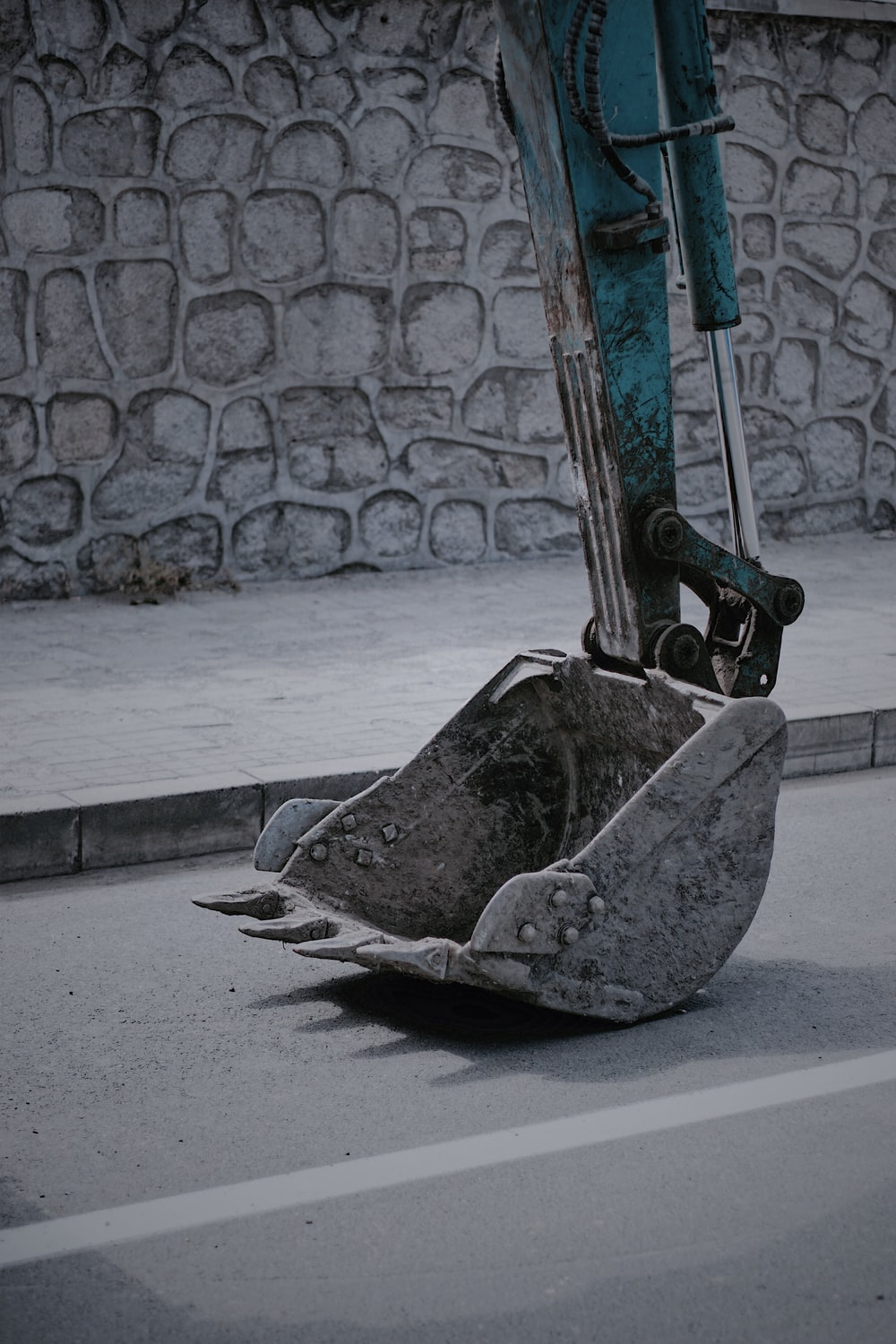 closeup photo of excavator bucket on road