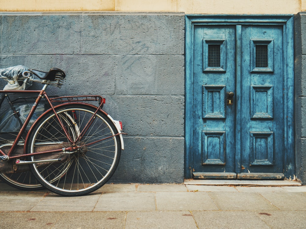 minimalist photography of parked bicycle near blue door