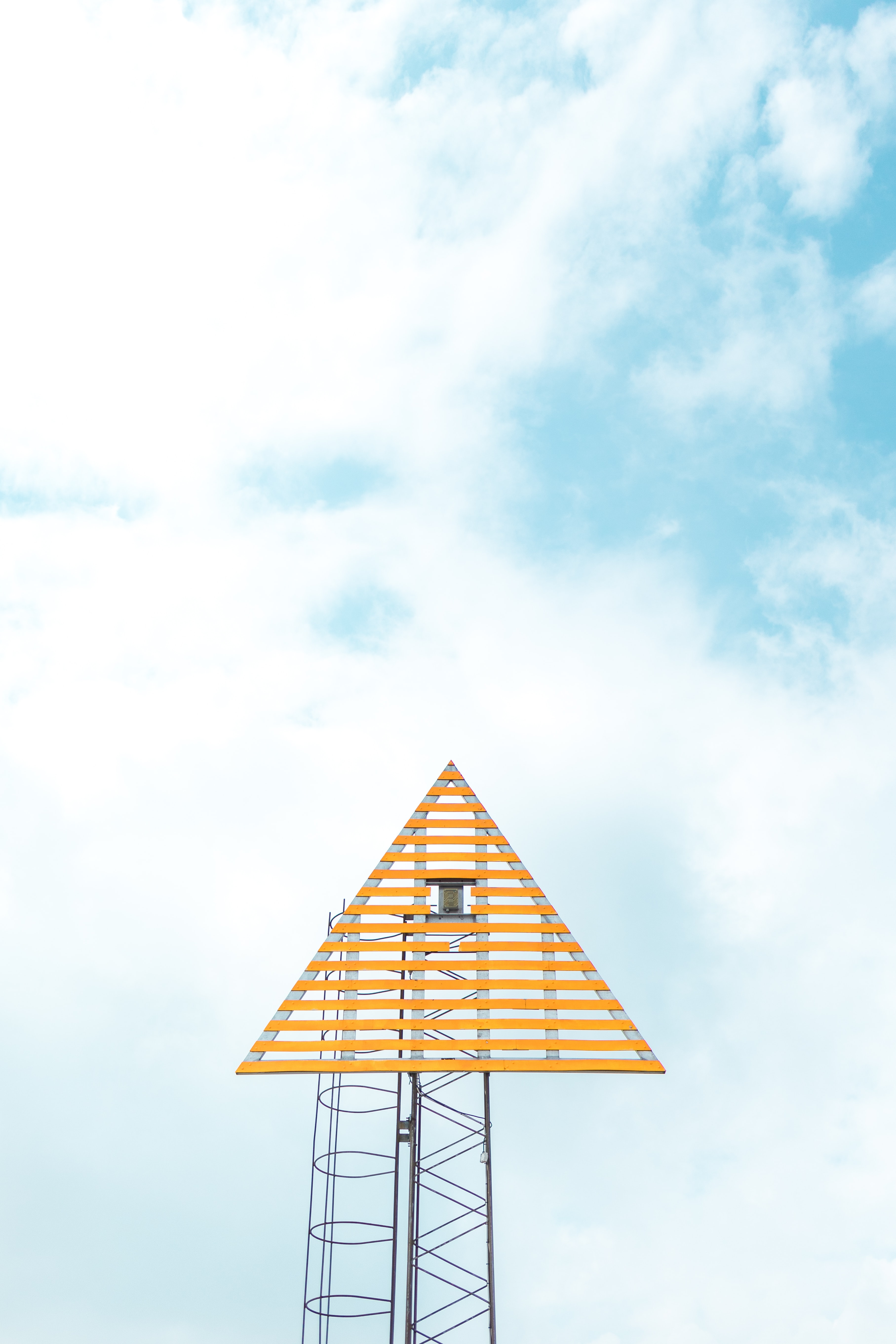 closeup photo of triangle tower with cloudy sky