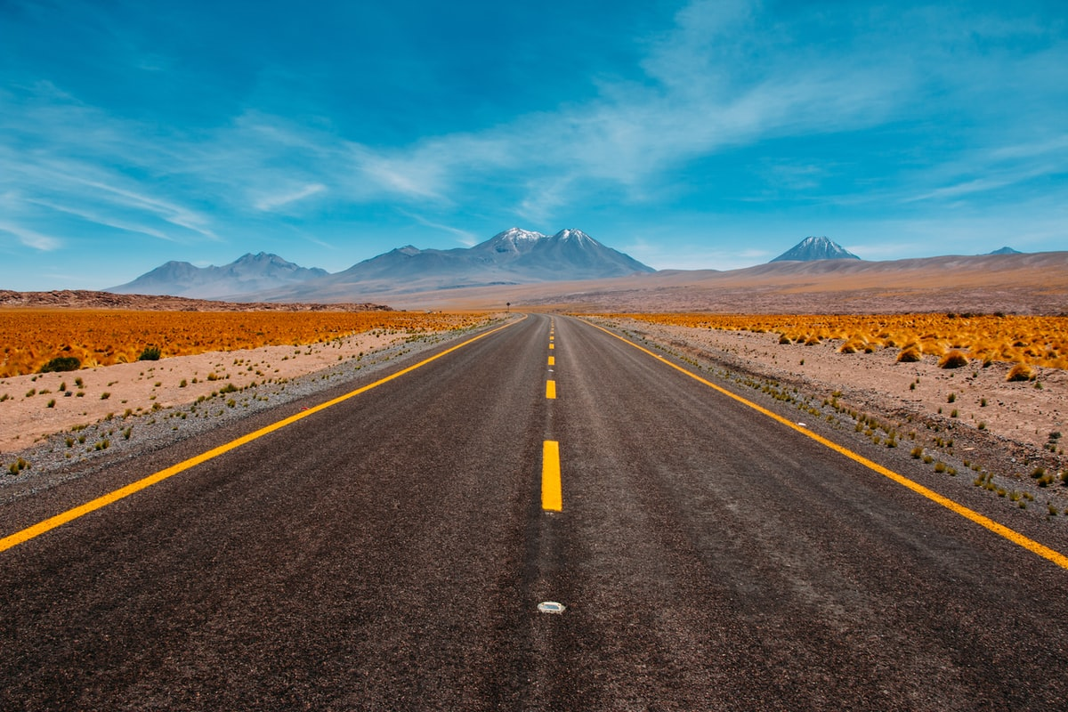 empty desert road with a view of the mountains