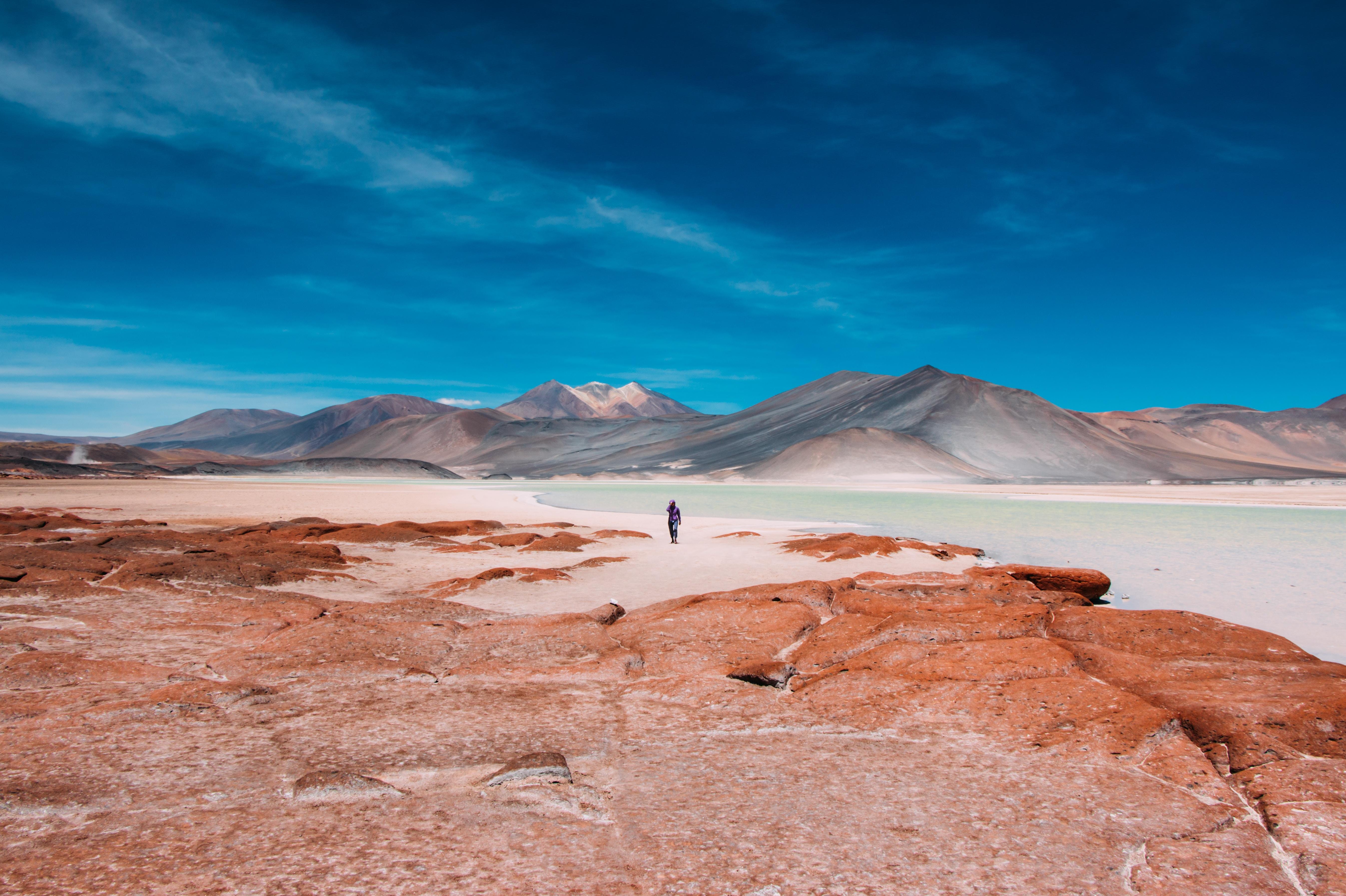Person walks toward mountains on the horizon of the Atacama Desert