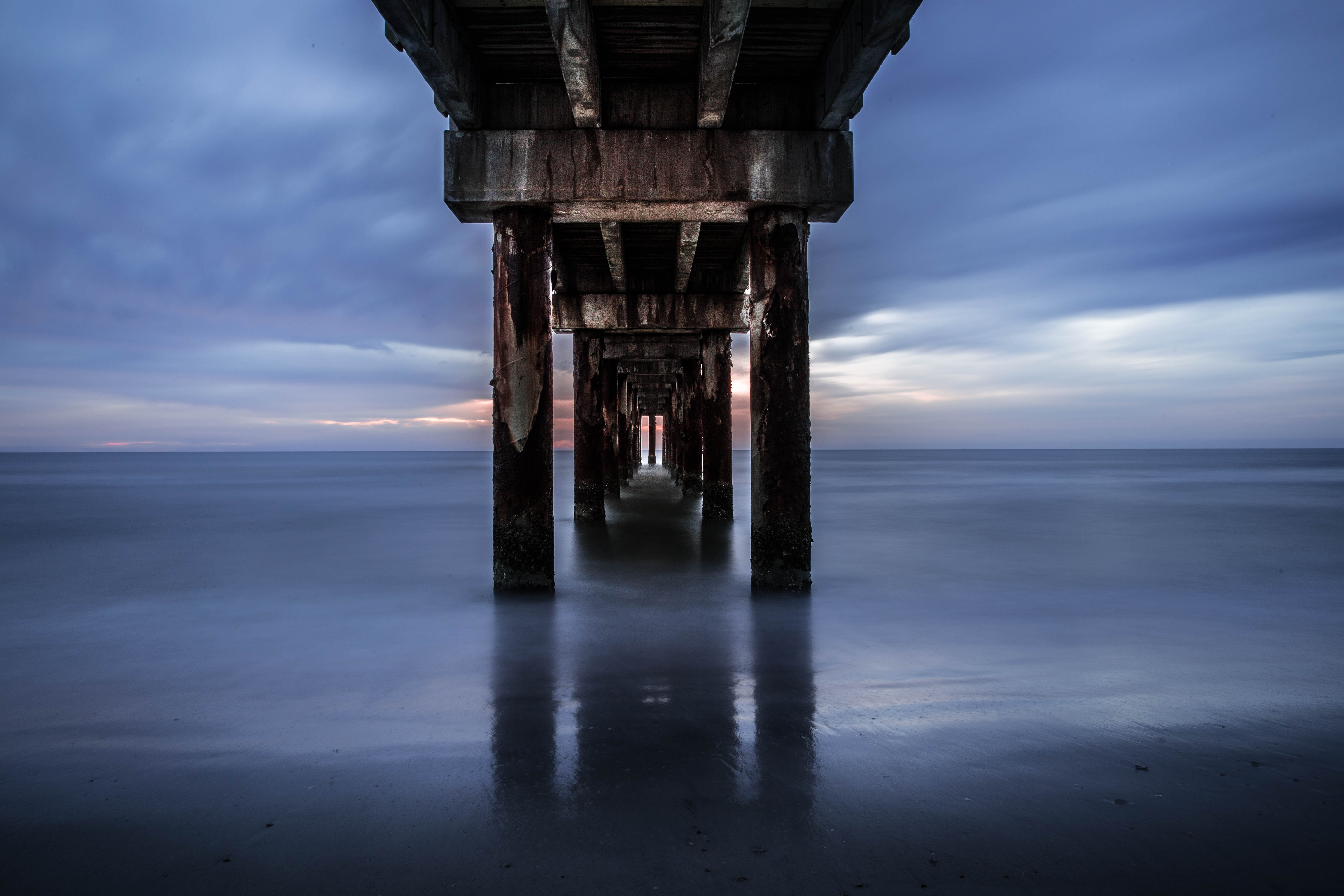 View into the distance under the pier between the pillars at Saint Augustine Beach