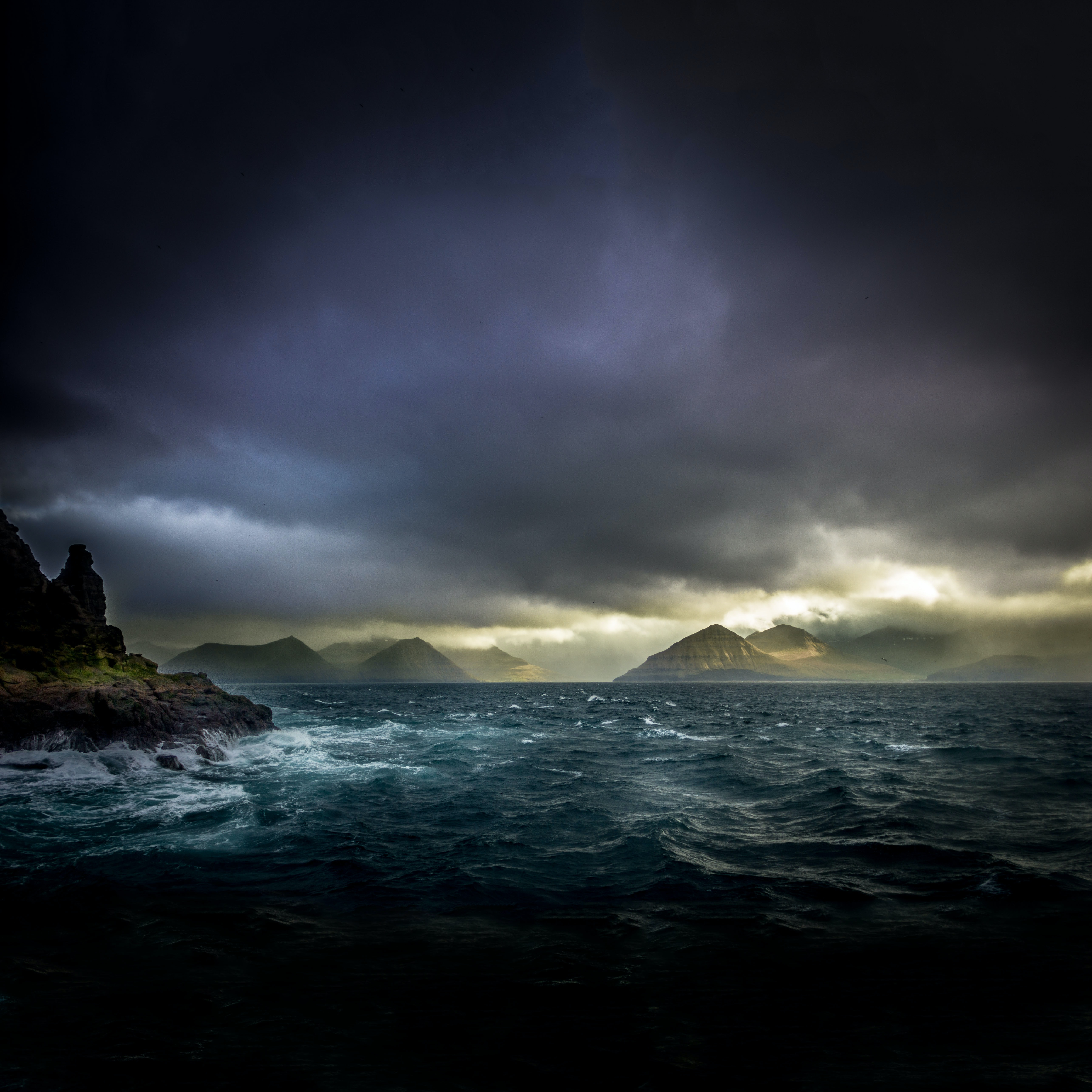 landscape photo of waters, mountains, and black clouds