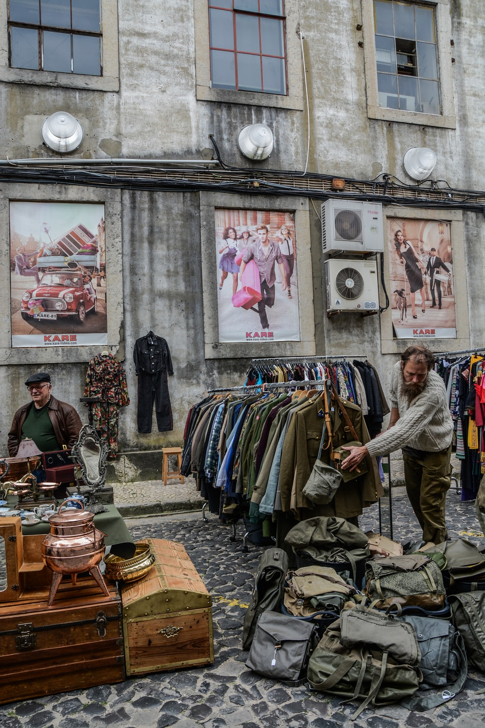 clothes and bags displayed on road near building during daytime