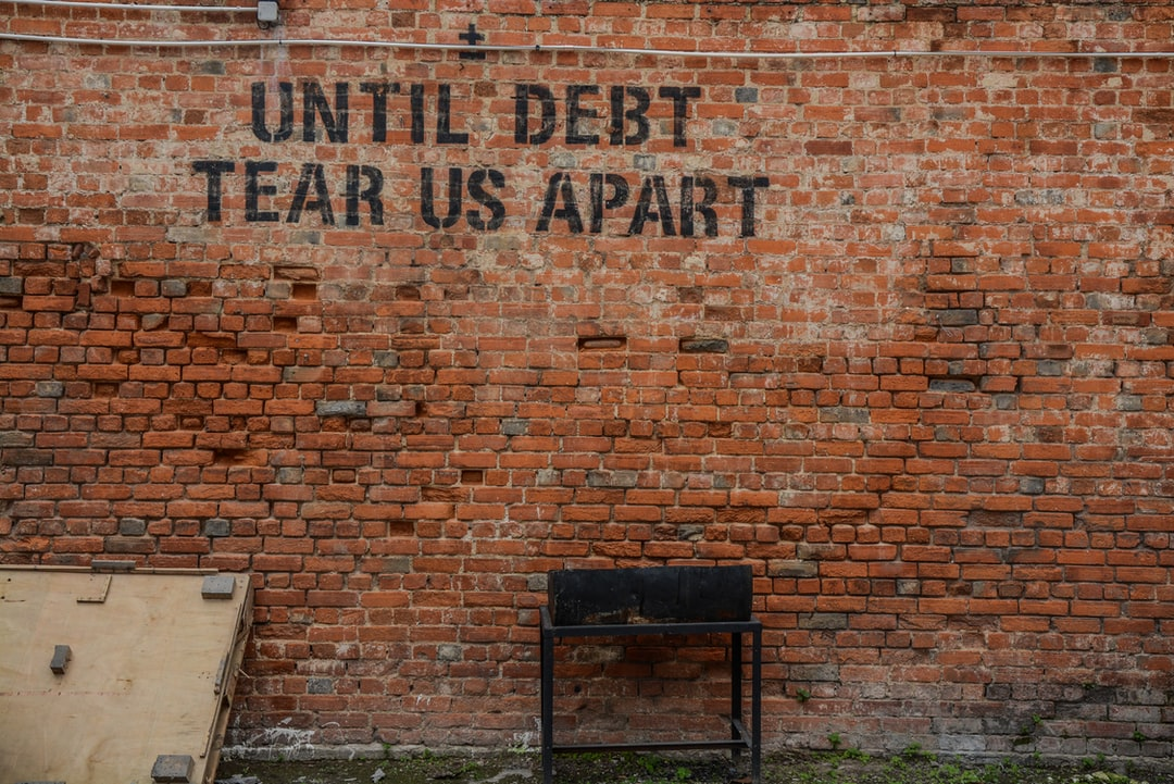 "Graffiti on an old brick wall reads ""until debt tear us apart"""