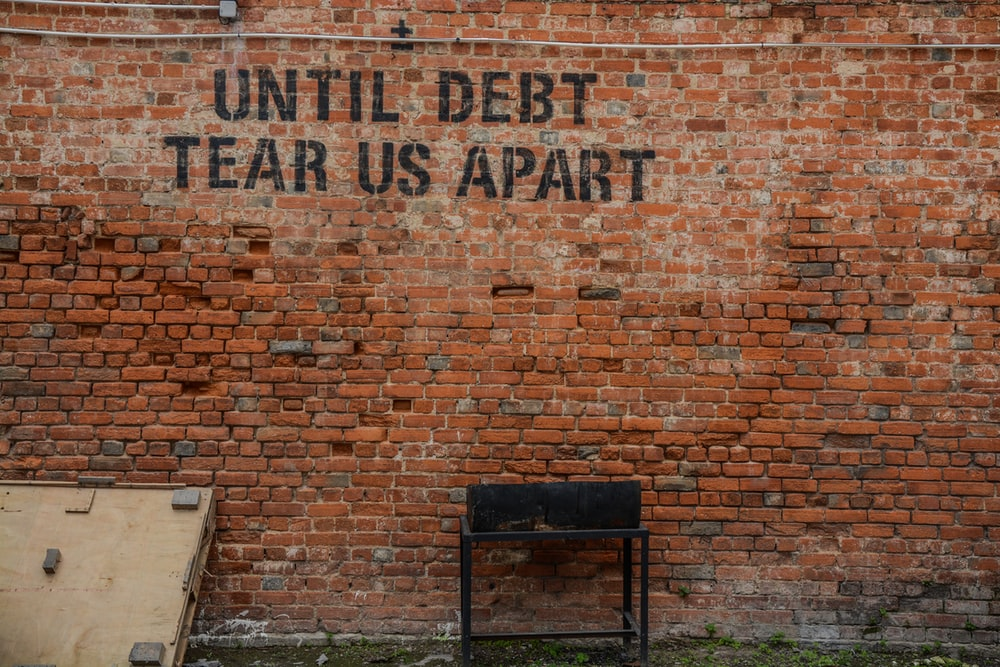 Until debt tear us apart printed red brick wall at daytime