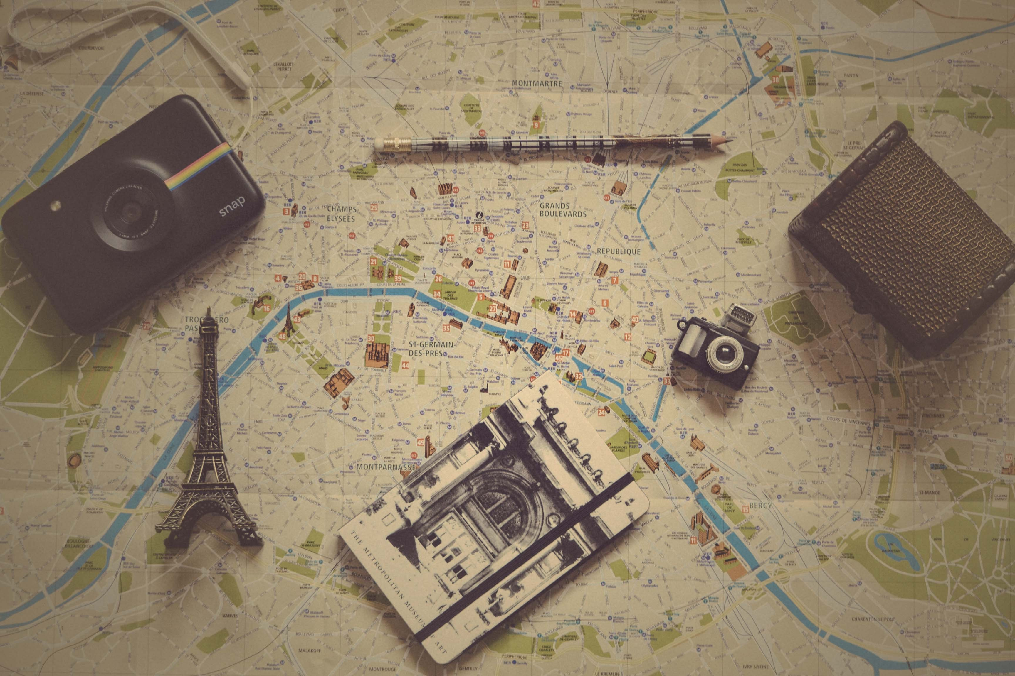 Vintage photo of small trinkets, a camera, and a journal on a map