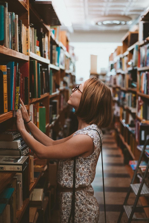 woman standing between library book shelves