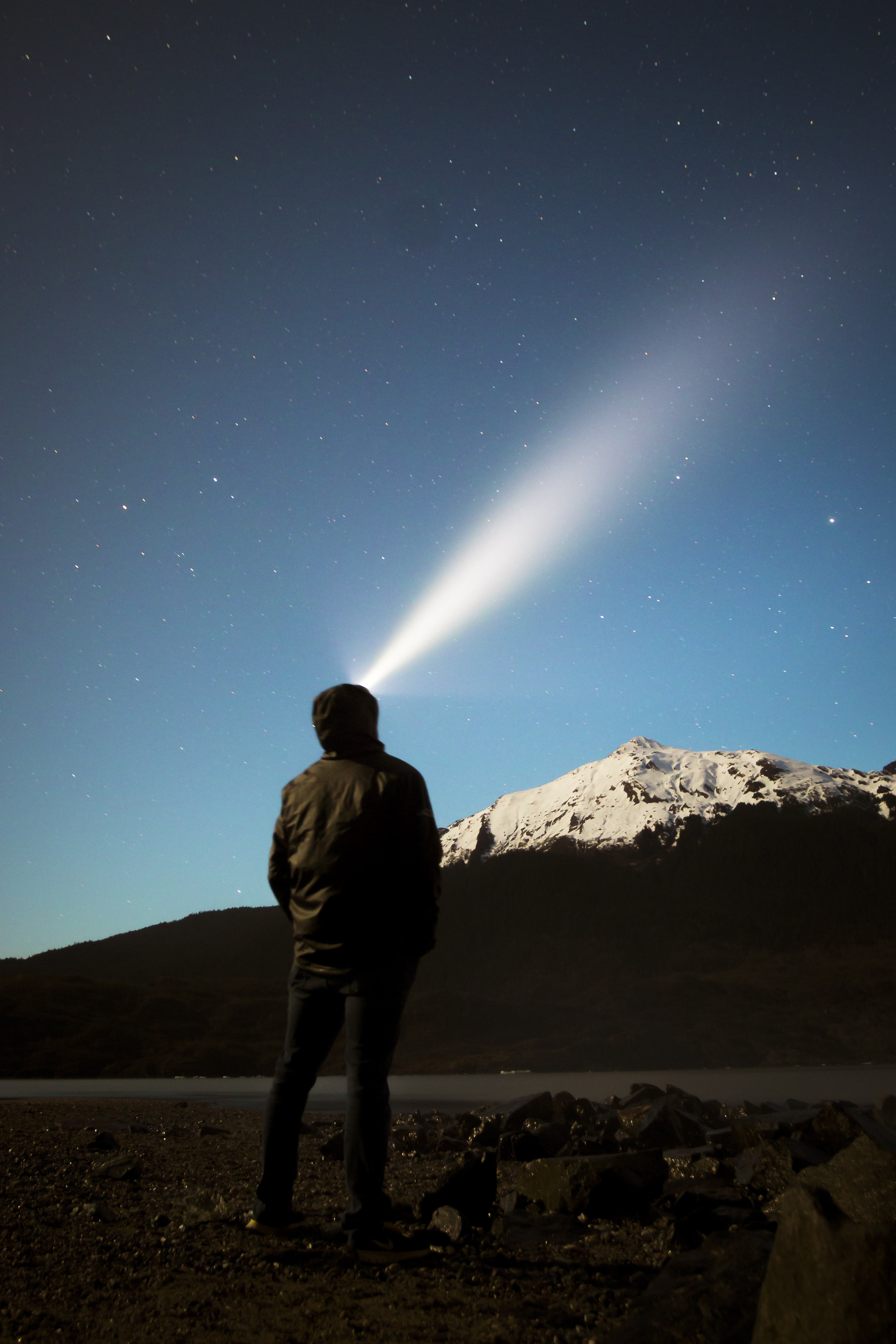 man standing in front of mountain watching light on sky