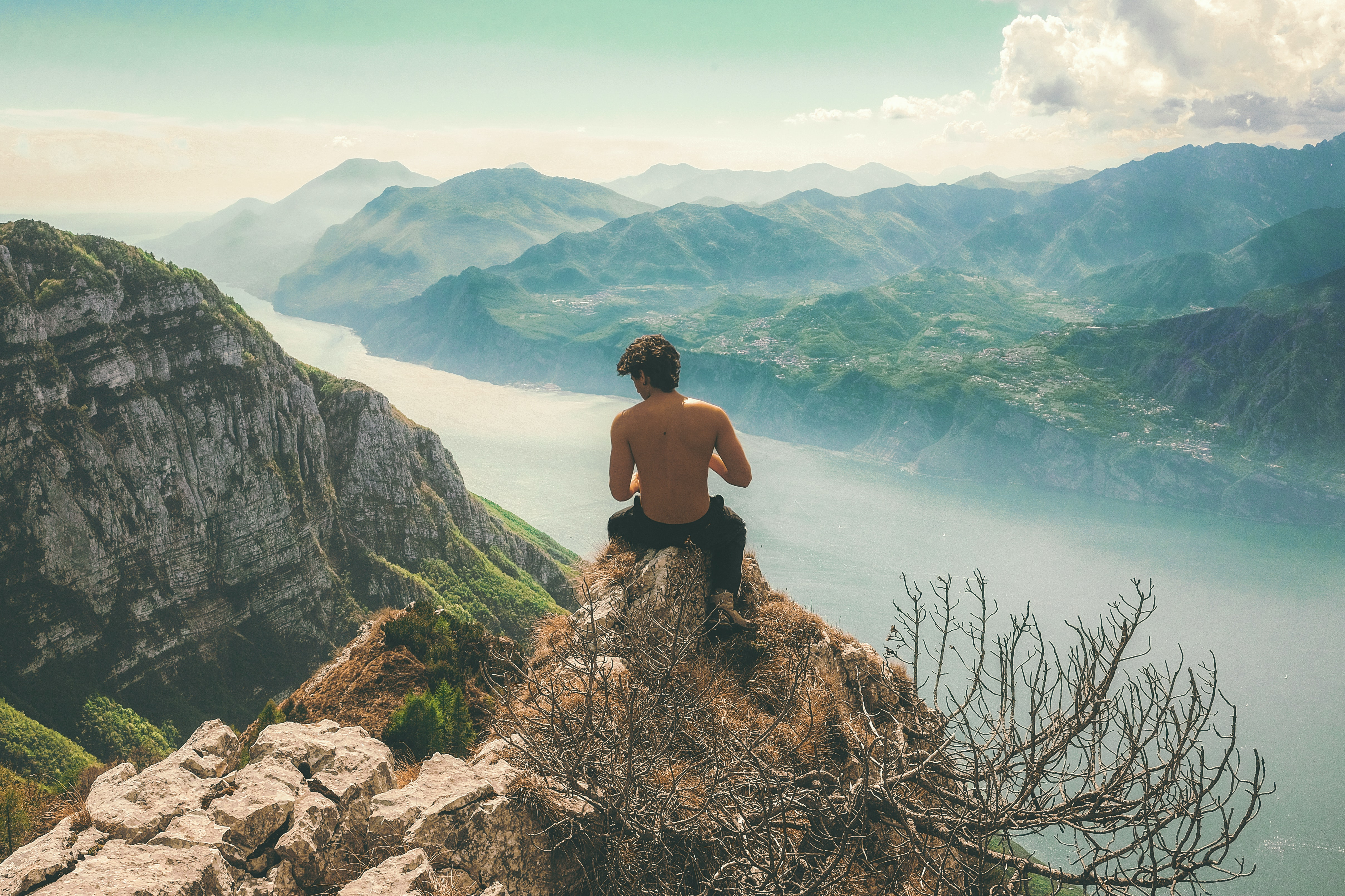 man seating on top of cliff in front of mountains