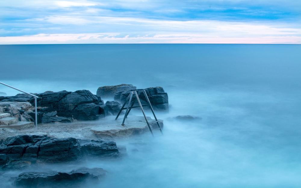 stone near body of water under cumulus clouds