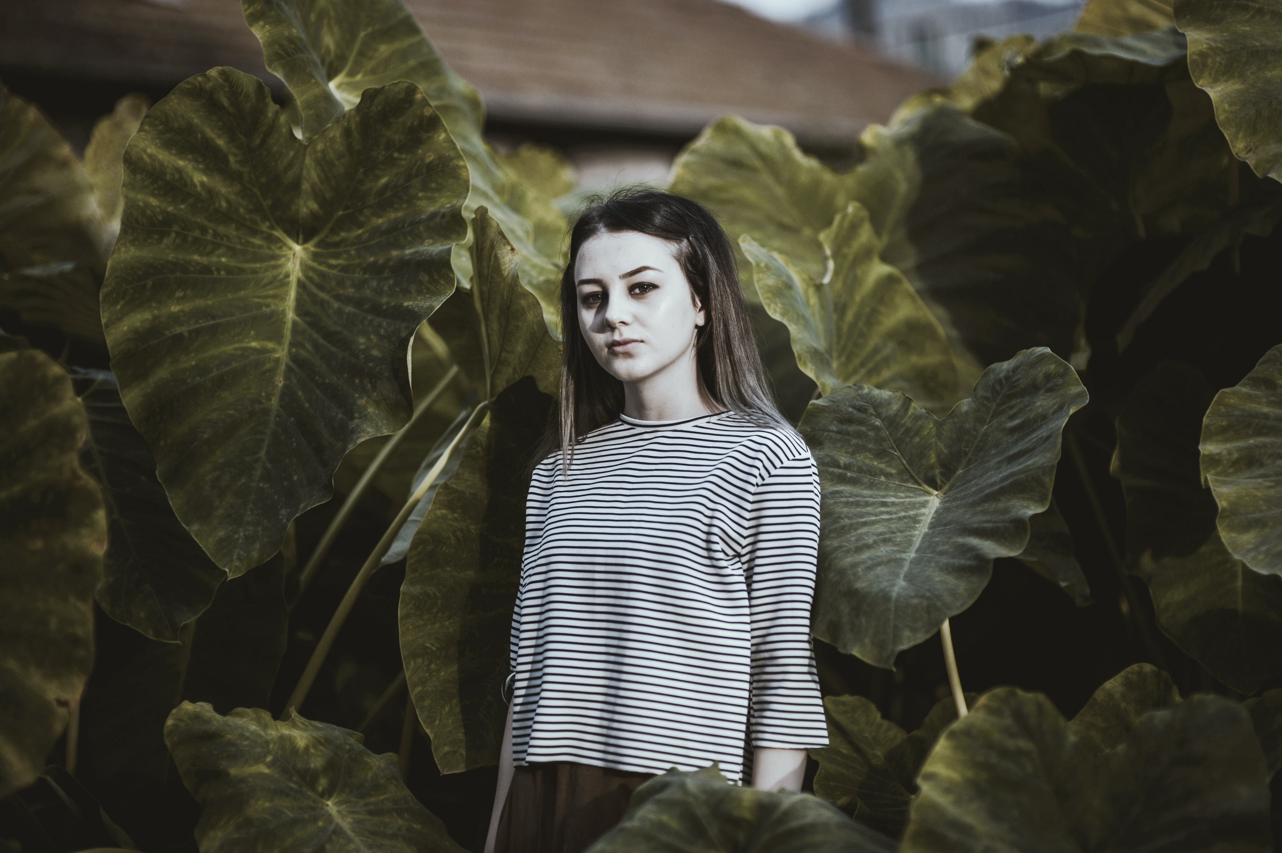 A woman in a striped shirt makes a serious expression in front of large green leaves