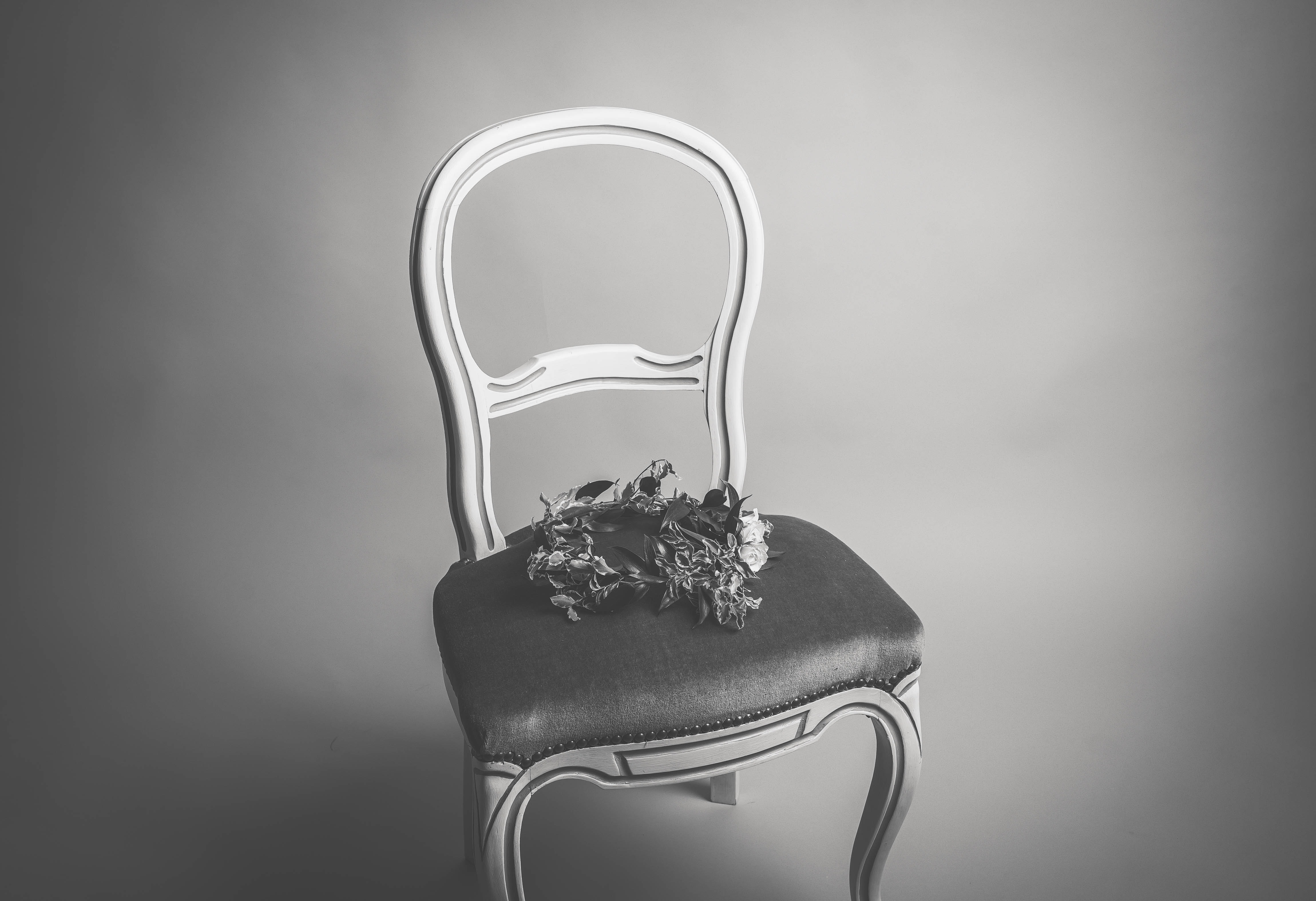 Black and white image of a vintage chair with a flower crown