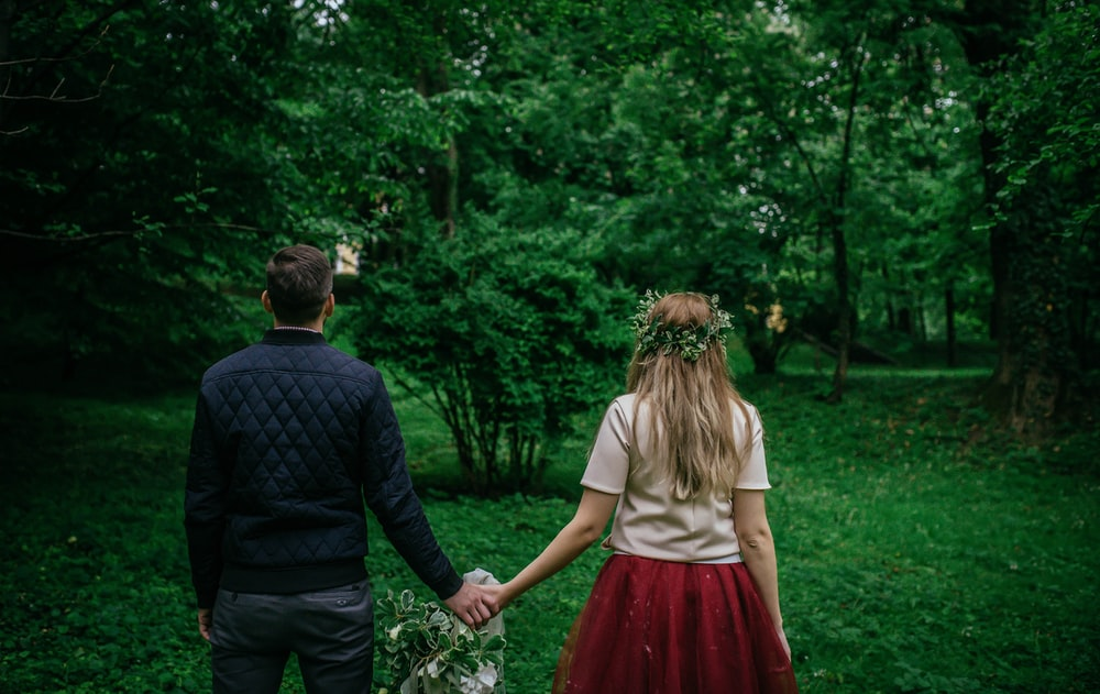 woman and man standing holding hands facing trees