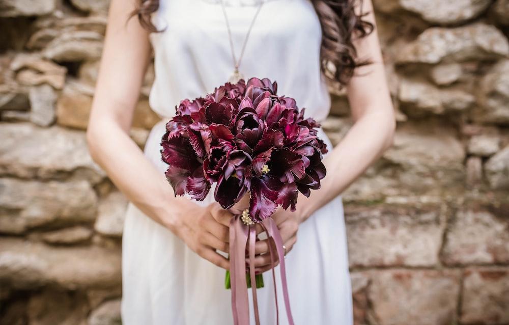 woman holding purple flower bouquet