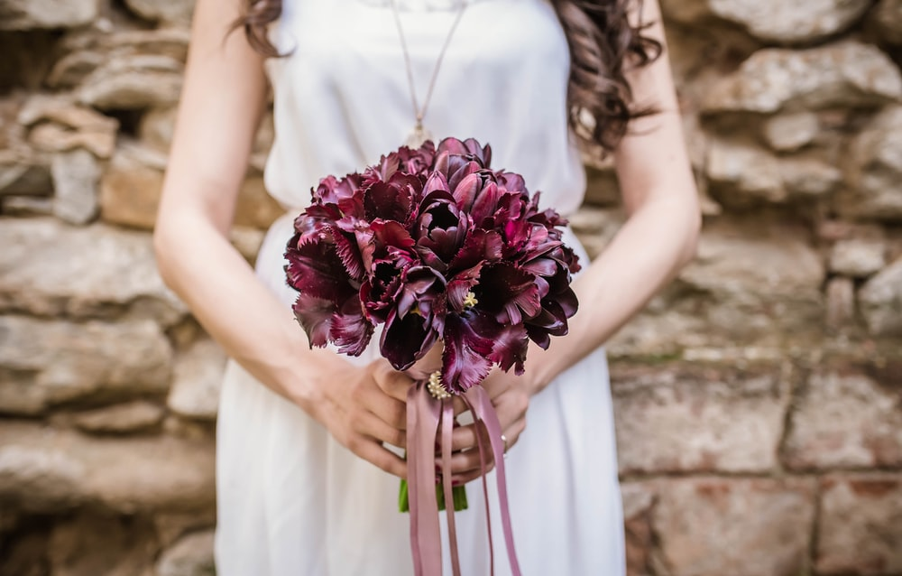 woman holding purple flower bouquet
