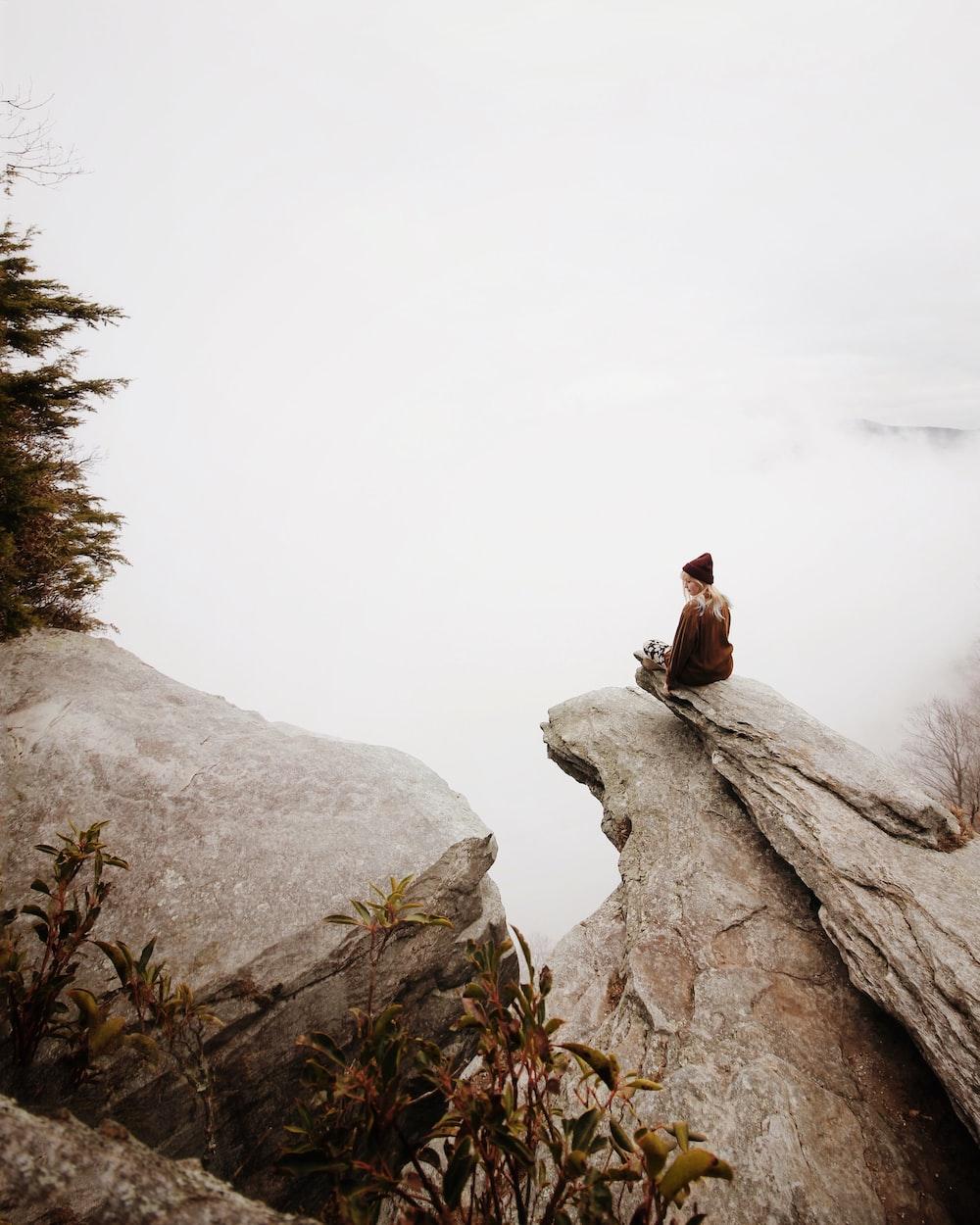 woman sitting on brown rock