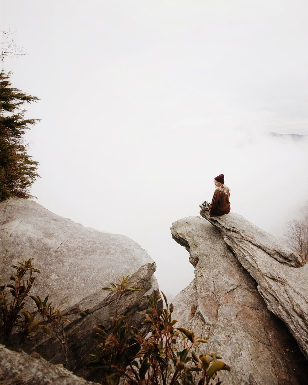 woman sitting on brown rock
