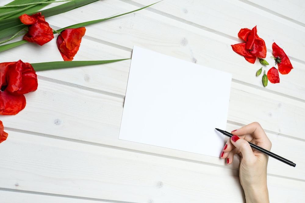 woman holding pen beside blank paper