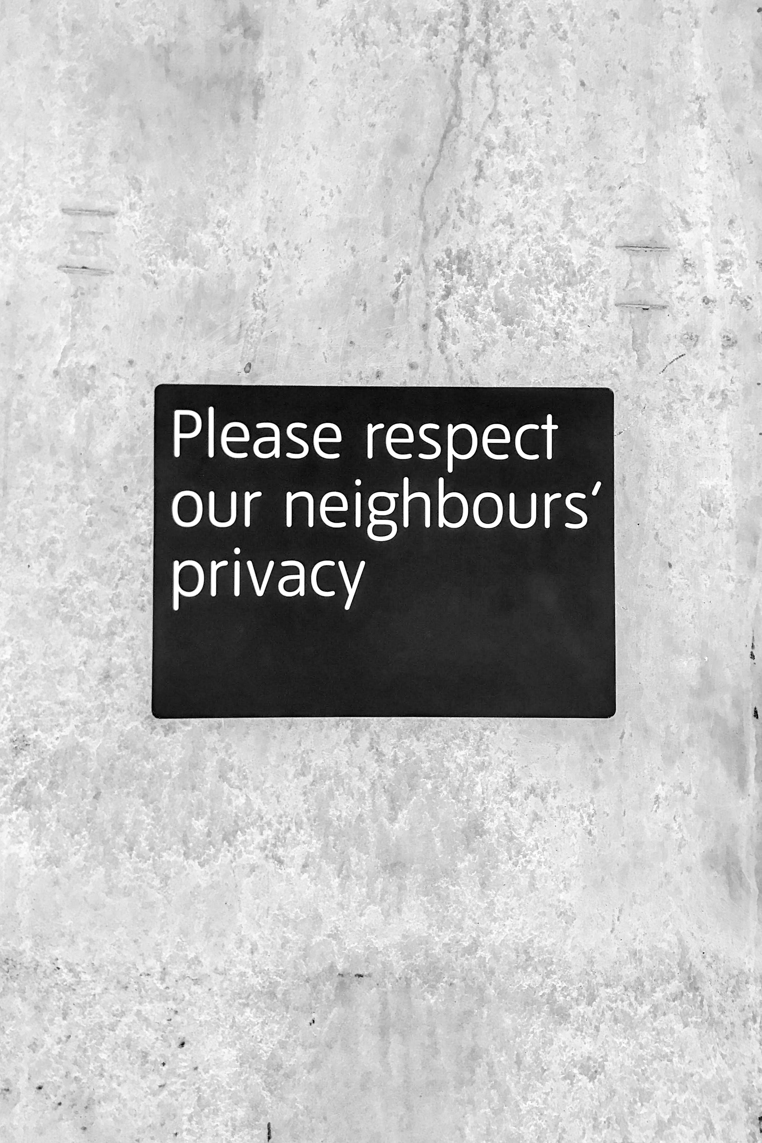"""A black sign with white text on a wall that reads """"Please respect our neighbors' privacy""""."""