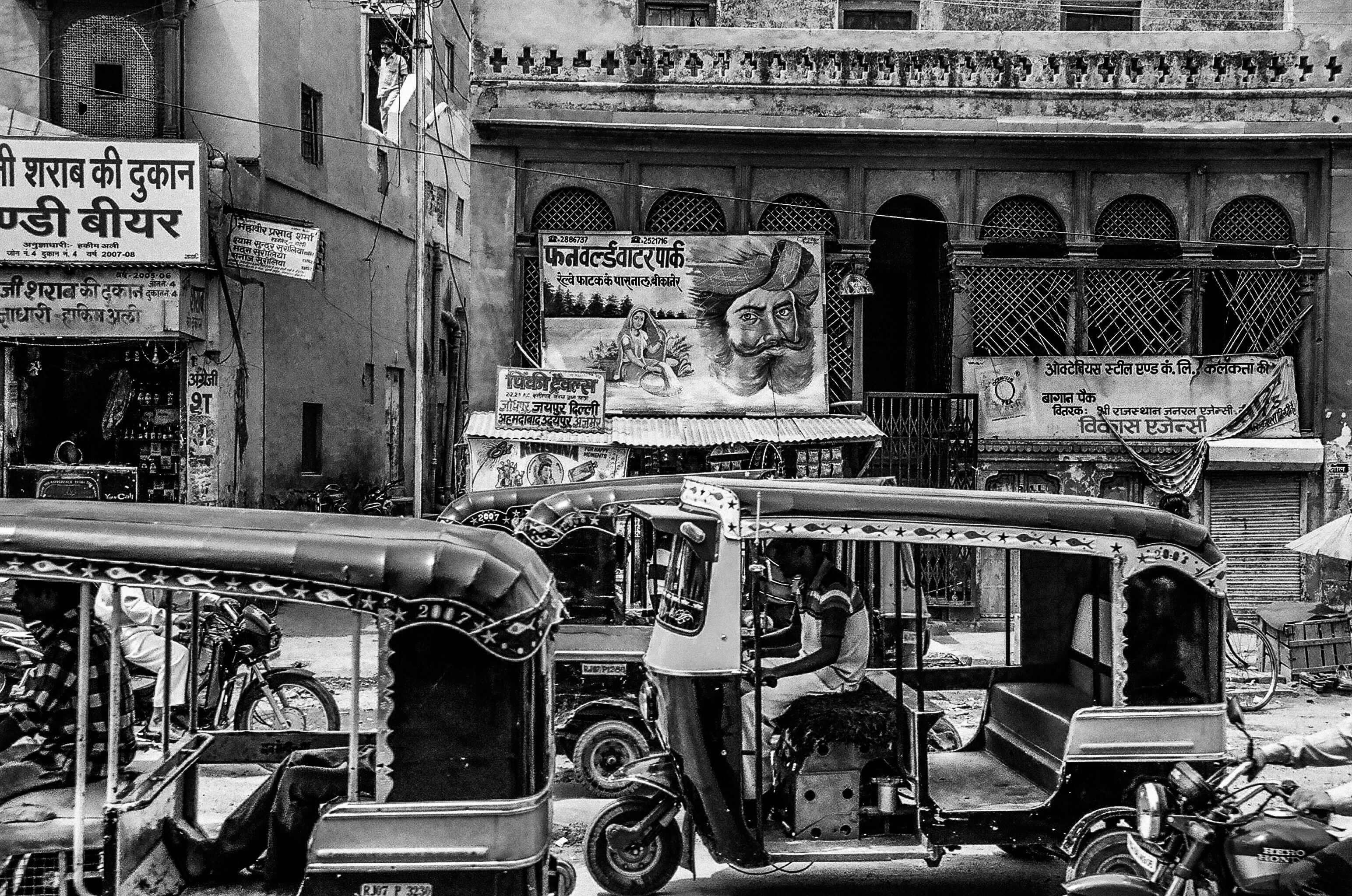 greyscale auto rickshaw and people
