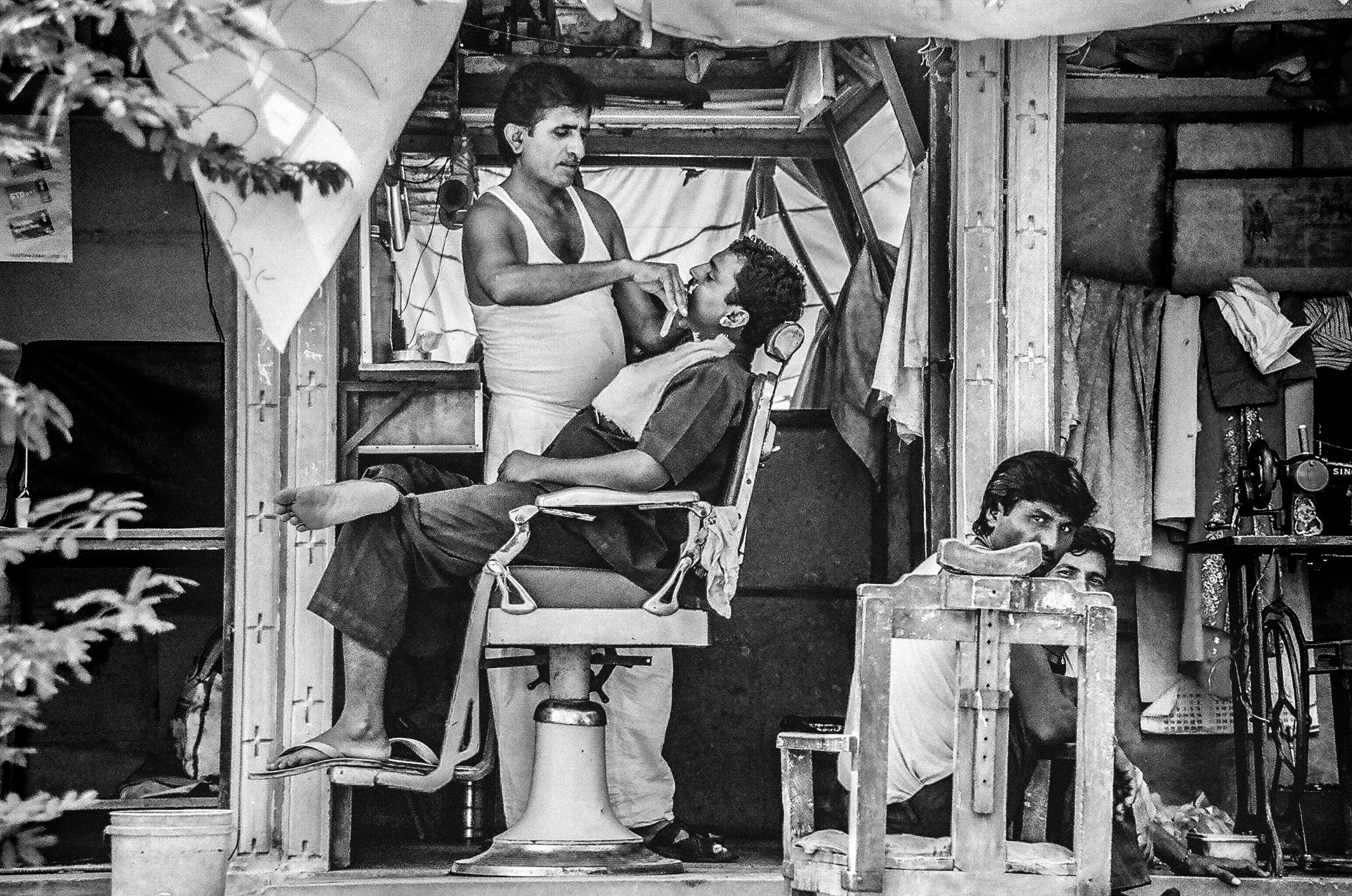Black and white shot of street barber shop and man getting a shaved sitting down