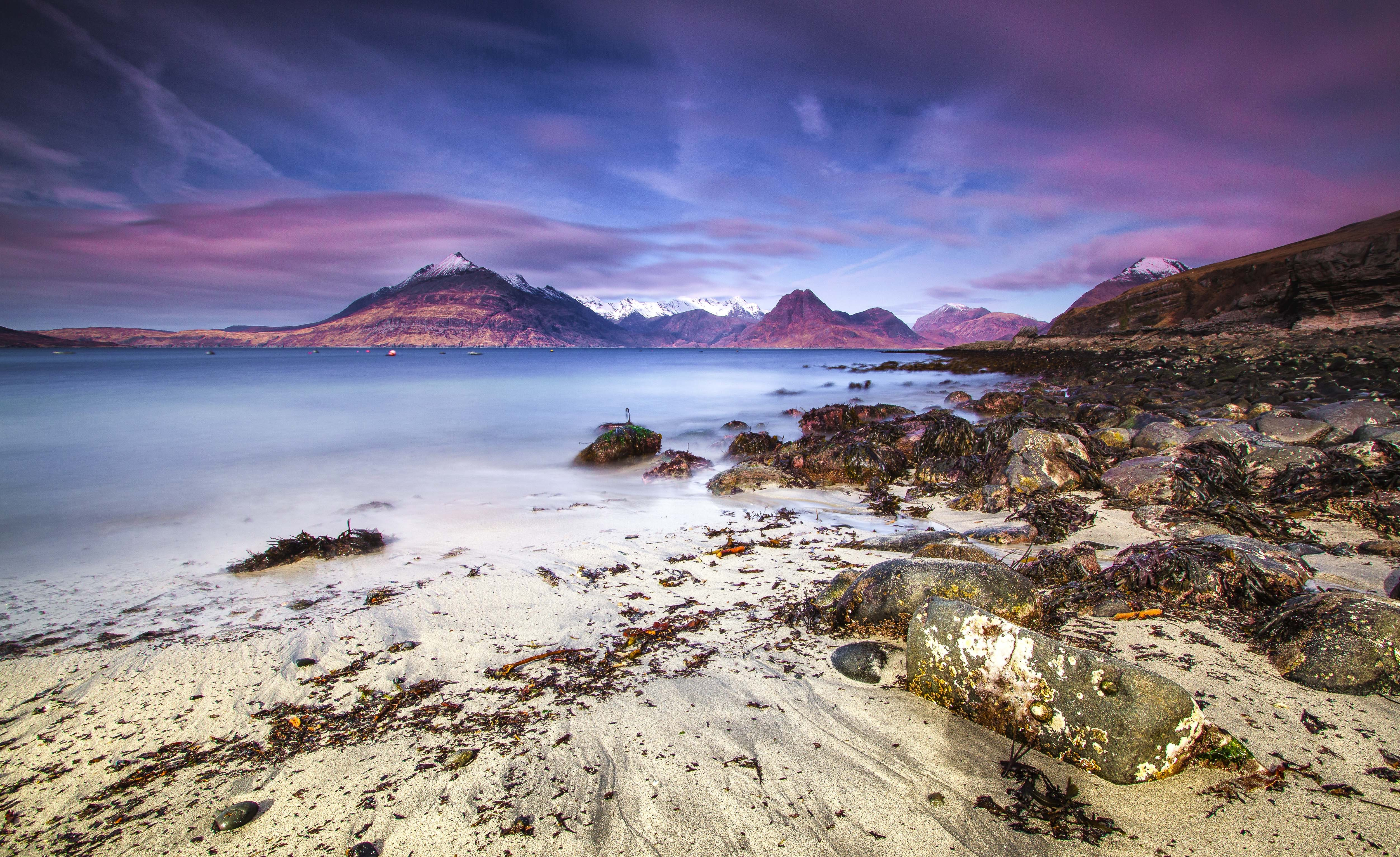 View of the mountain range from rocky sand beach in Elgol Village