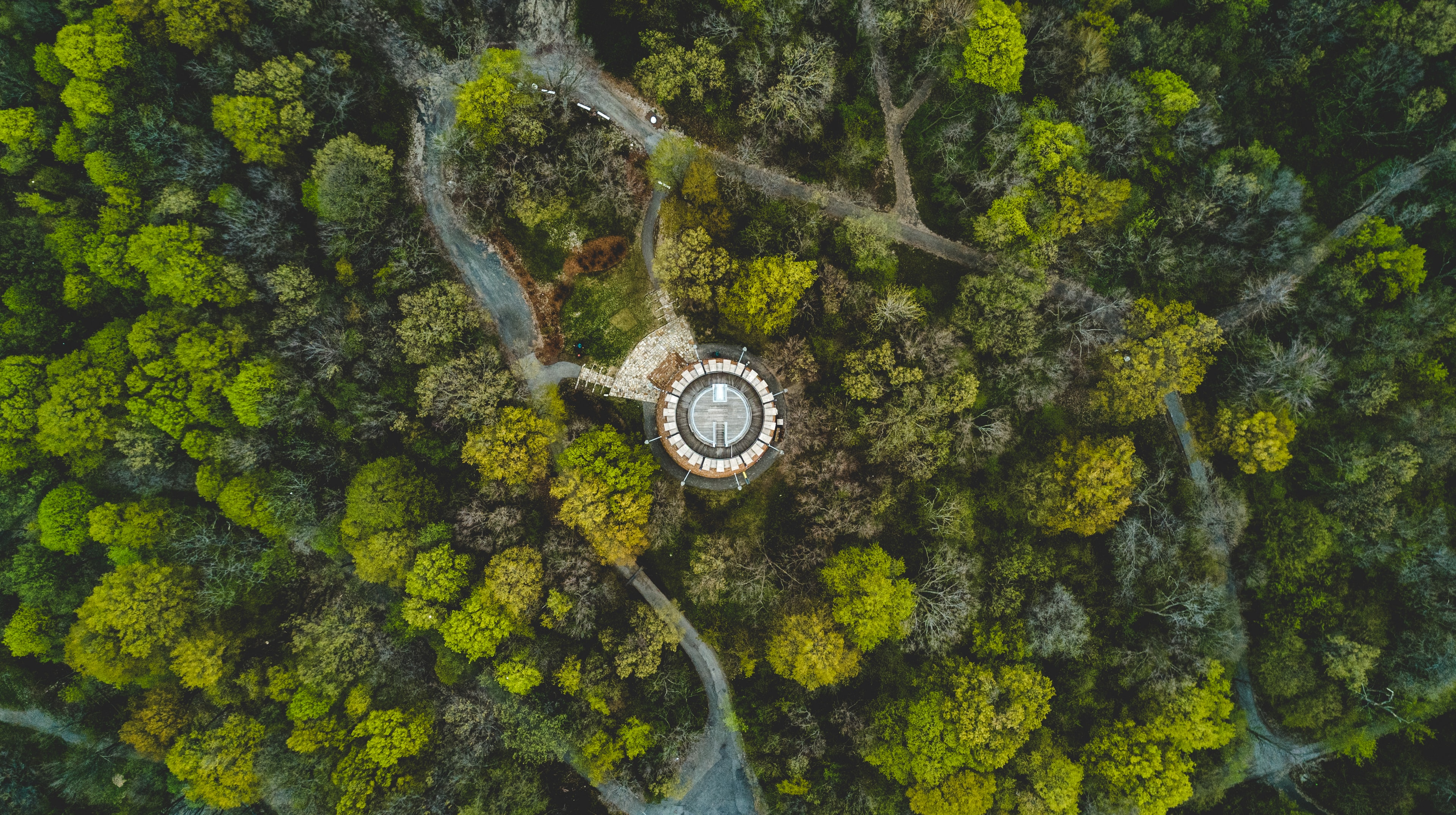 A drone shot of a round building in a wooded area with narrow footpaths