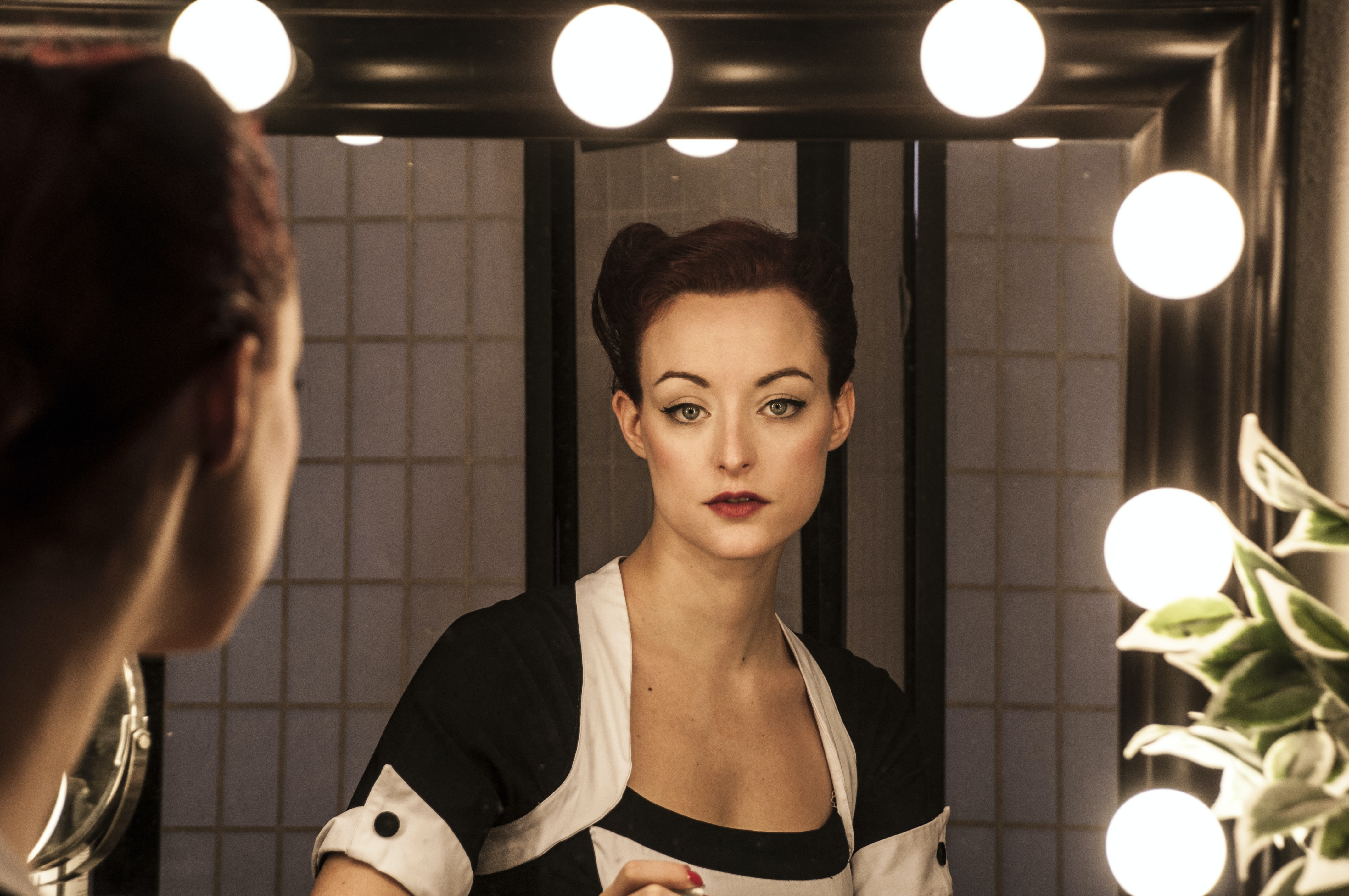A woman in makeup and a black-and-white dress looks into a lighted mirror