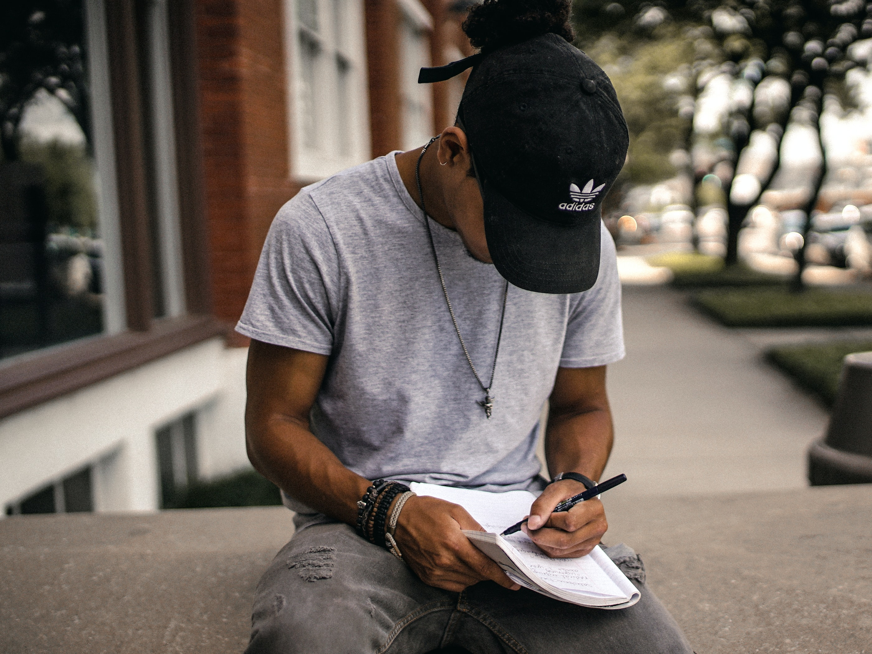 A man in a baseball cap taking notes while sitting on a concrete ledge outdoors