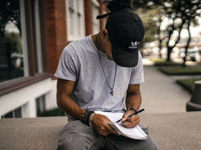person in black adidas cap sitting on bench writing on notebook writer teams background