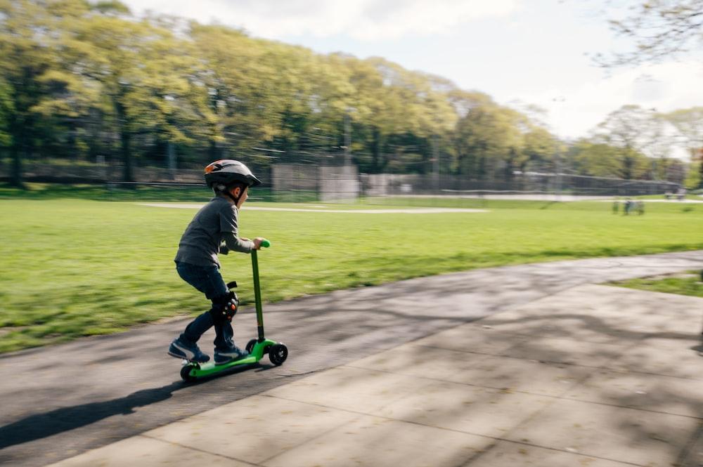 boy riding green kick scooter