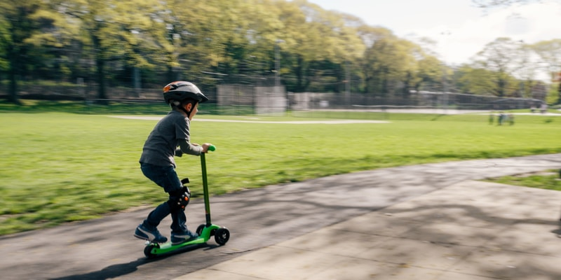 boy riding green kick scooter