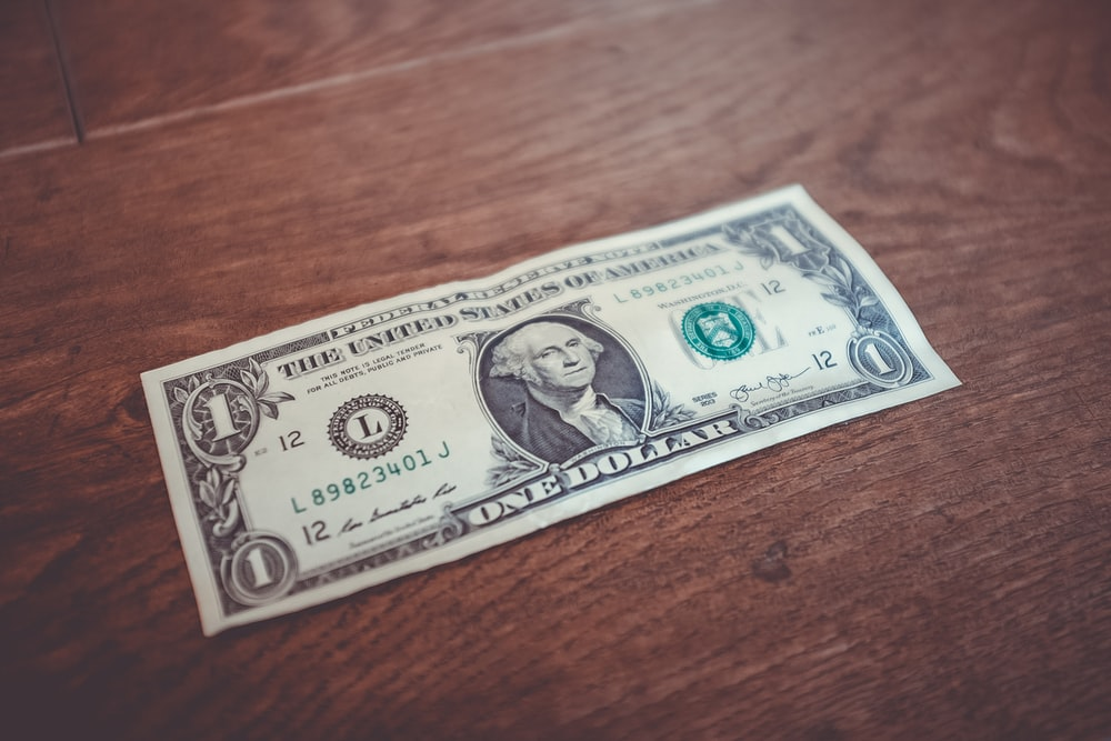 A one dollar bill sitting on the floor.