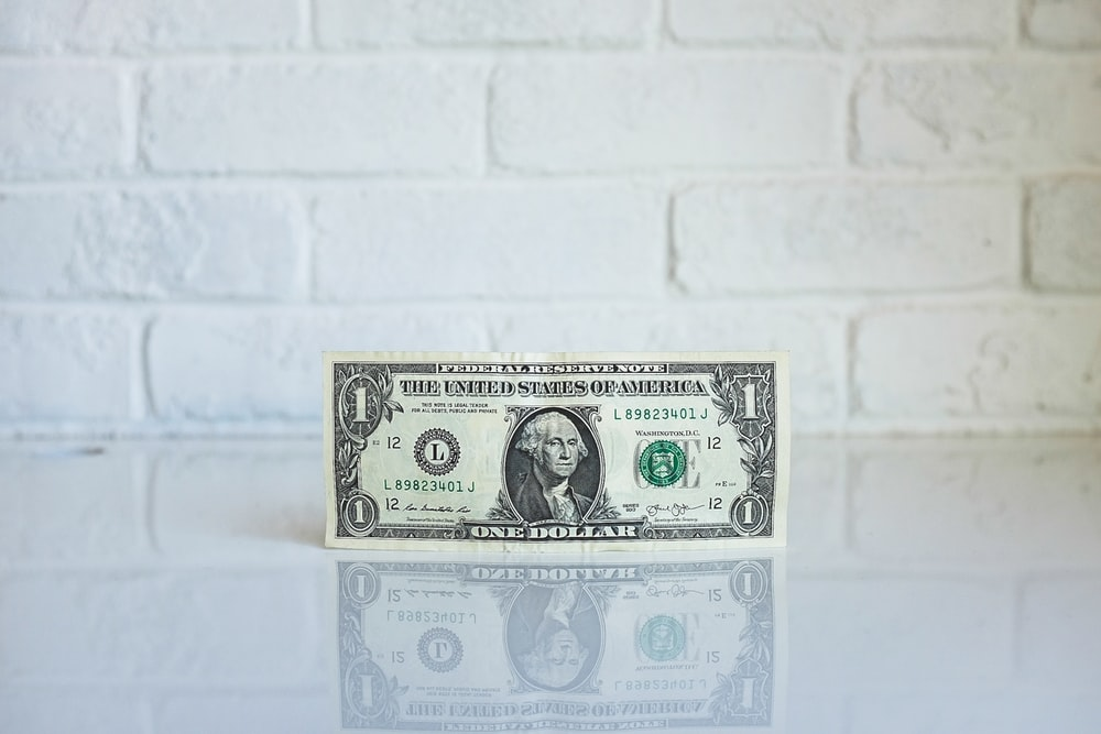 A one dollar bill leaning against the wall on a glossy surface