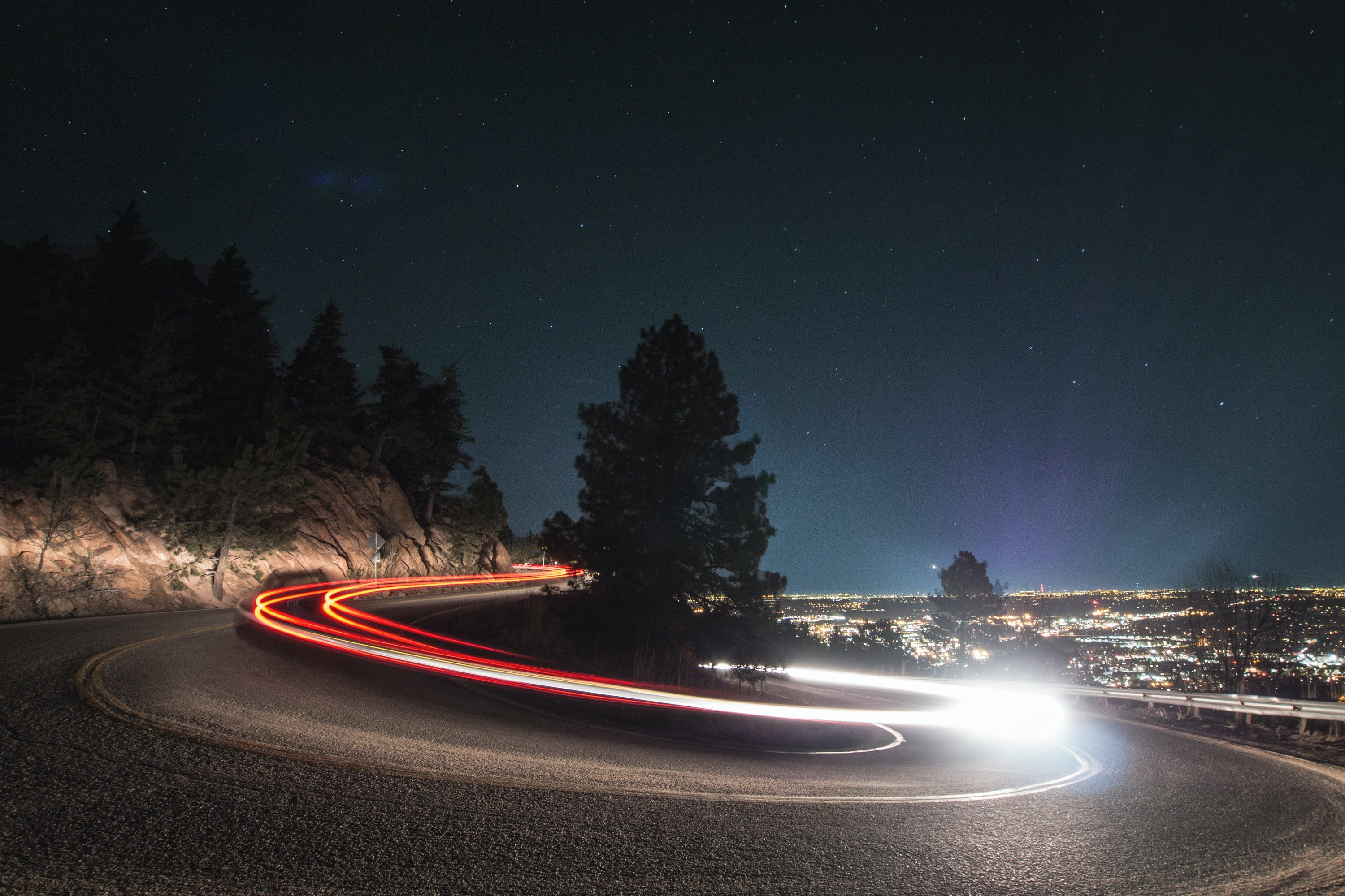 A slow shutter shot of a curved road in Boulder, with fast-driving car light trails