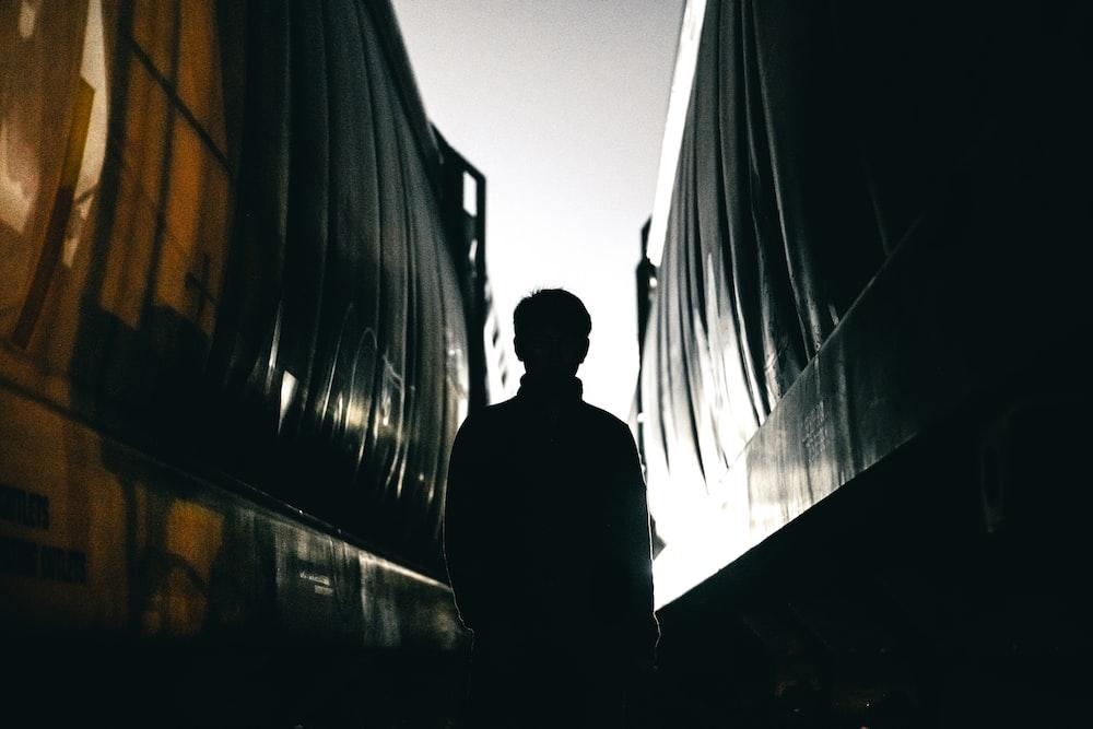 man standing between building silhouette