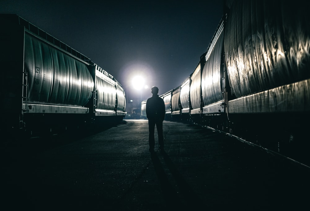 silhouette of man standing beside train