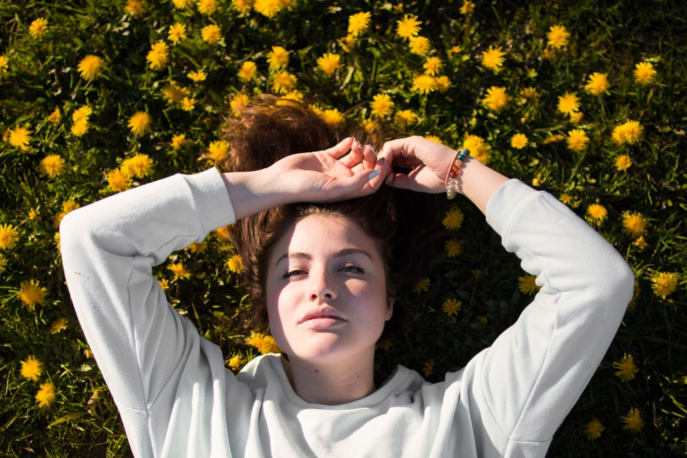 woman in white top laying on flowers