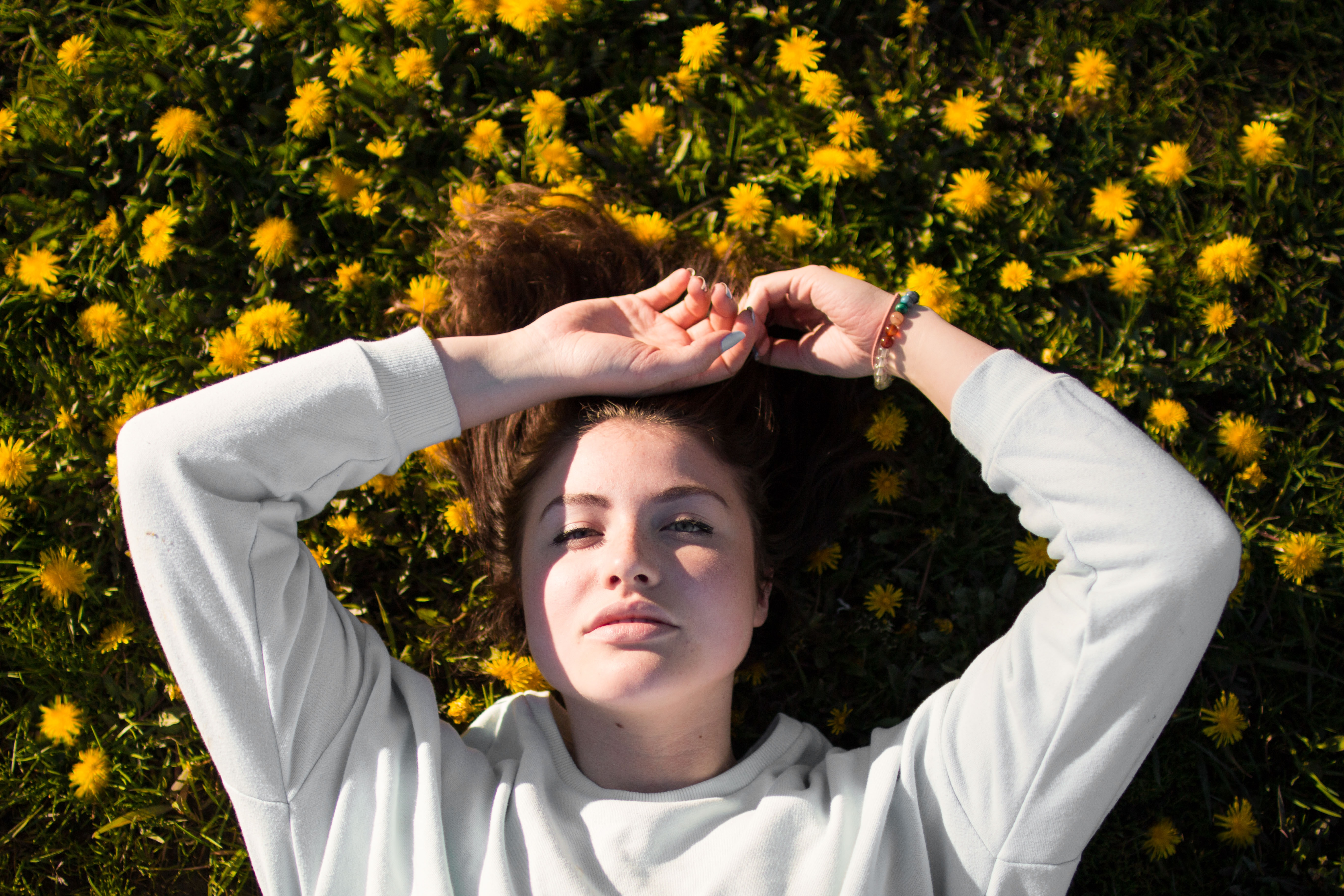 A woman in a sweatshirt lays in a field of yellow dandelions