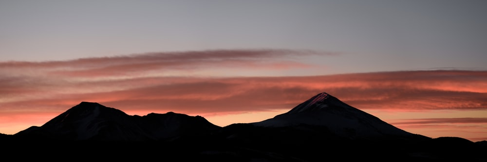 silhouette photo of mountains in sunset