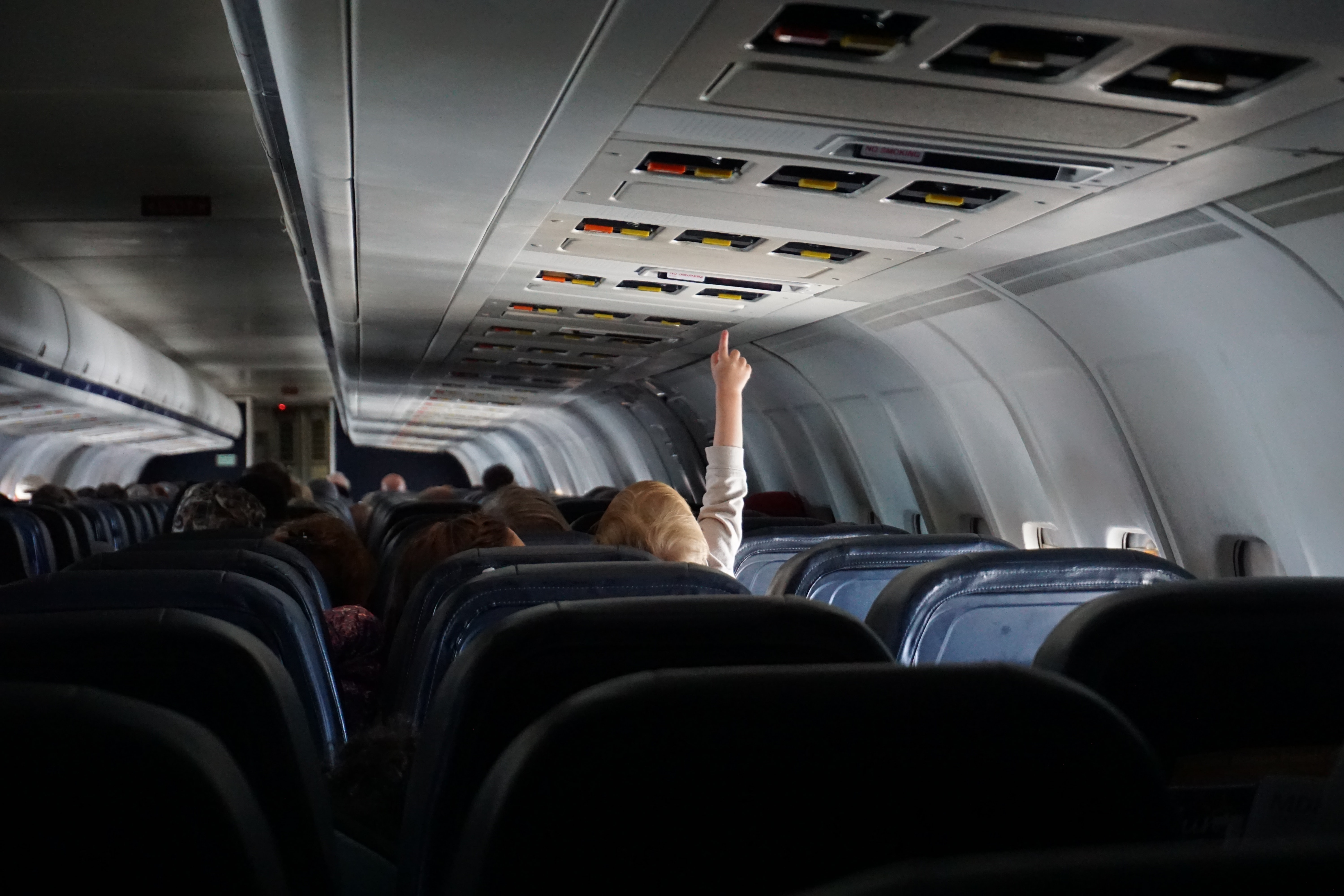 A child on a plane lifting their hand to adjust overhead controls above the seat